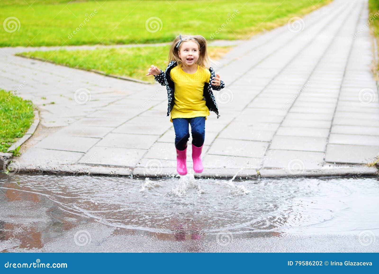 Lycklig gullig liten flickabanhoppning i pöl efter regn i sommar