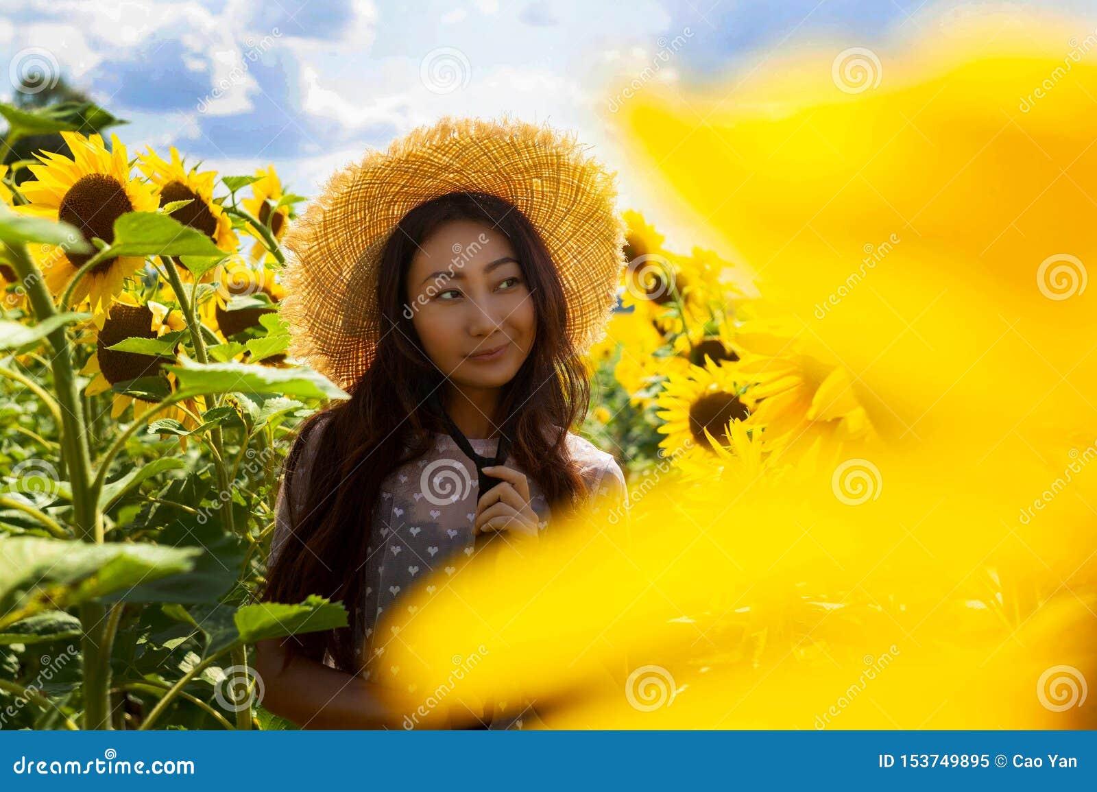 Lycklig härlig asiatisk kvinna med sugrörhatten i solrosfält
