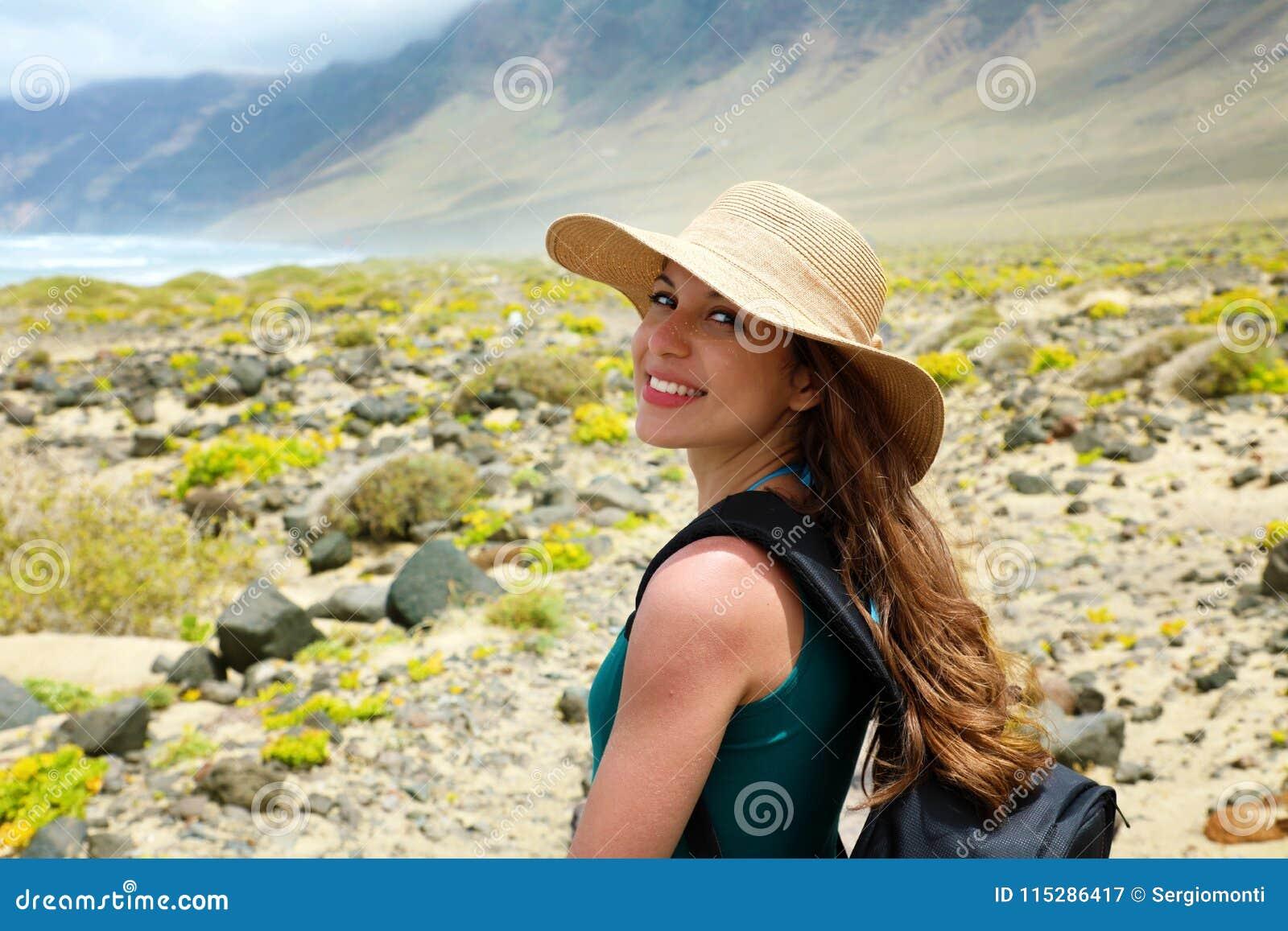 Lycklig härlig handelsresandeflicka med sugrörhatten som ser till kameran Ung kvinnlig fotvandrare som undersöker Lanzarote, kana