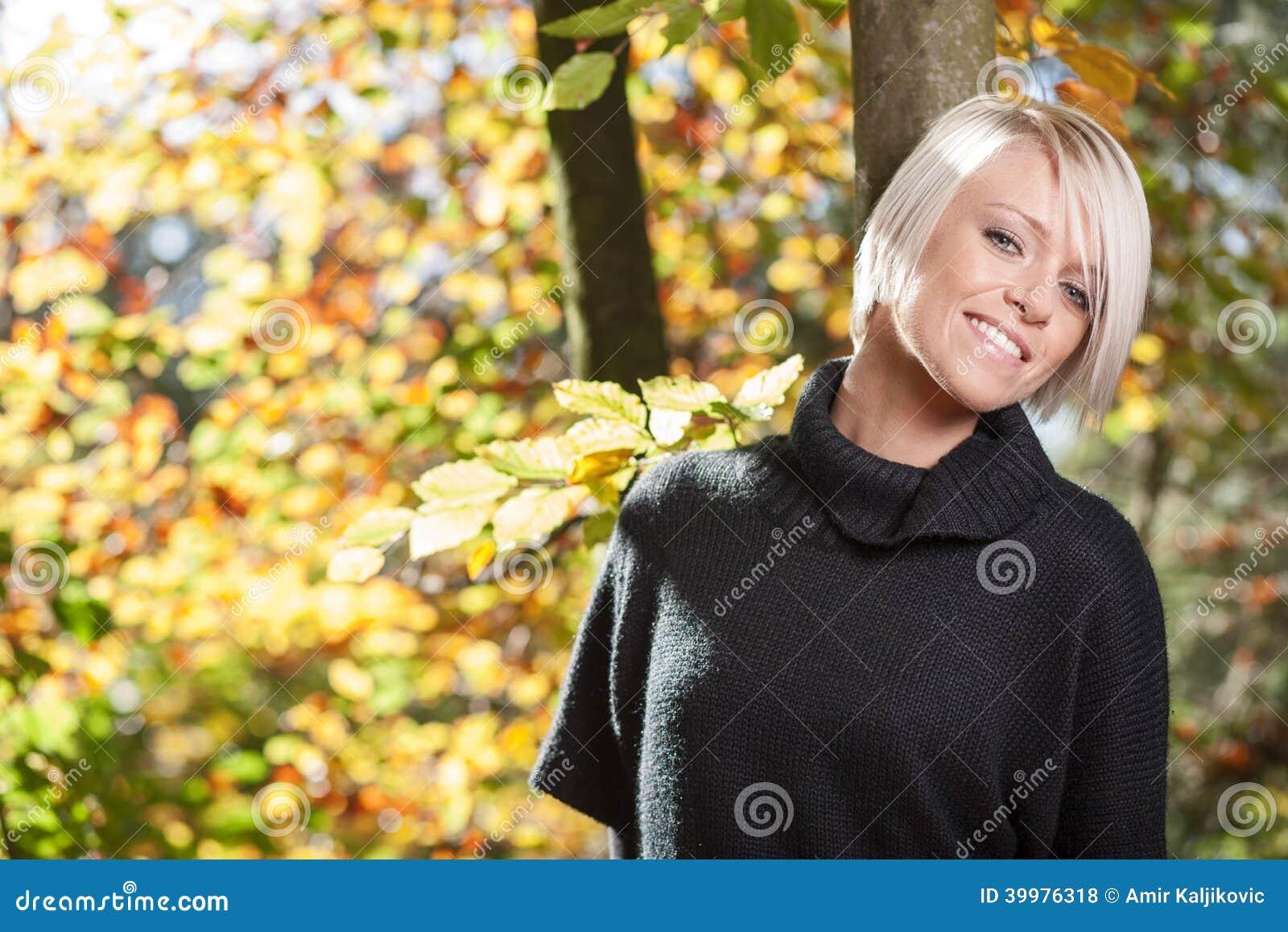 Lycklig härlig kvinna i höstträn