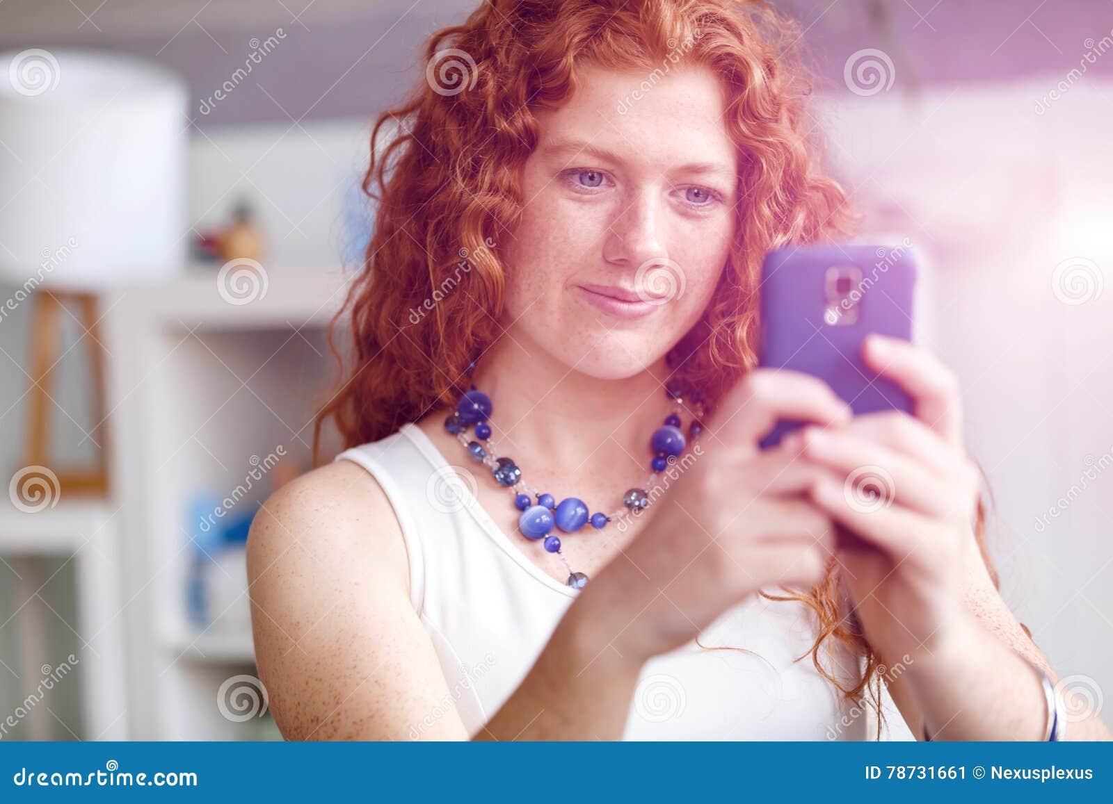 Lycklig härlig ung affärskvinna som använder smart le för telefon
