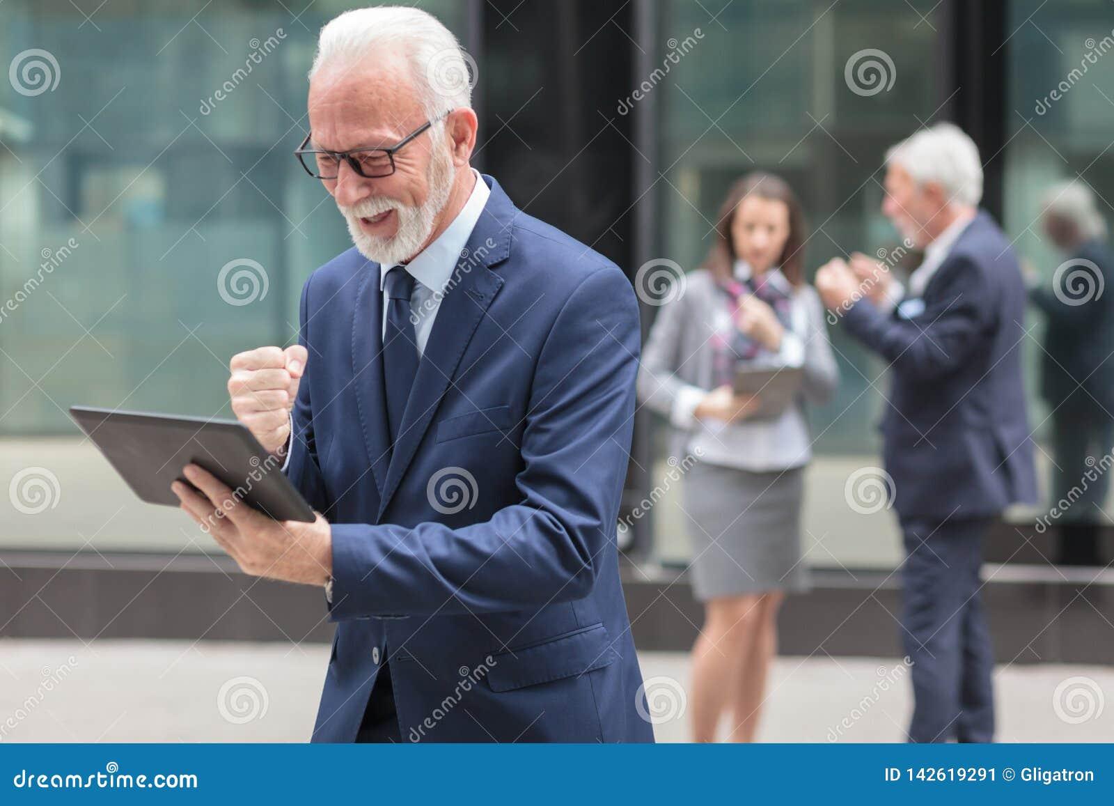 Lycklig hög affärsman som använder minnestavlan som framme står av en kontorsbyggnad