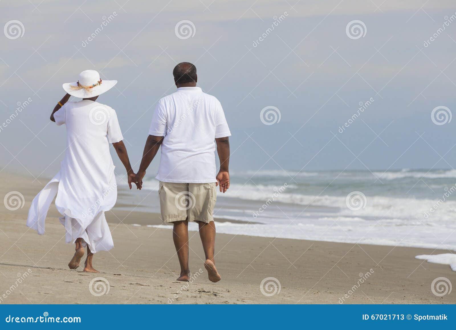 Lycklig hög kvinna för afrikansk amerikanparman på stranden