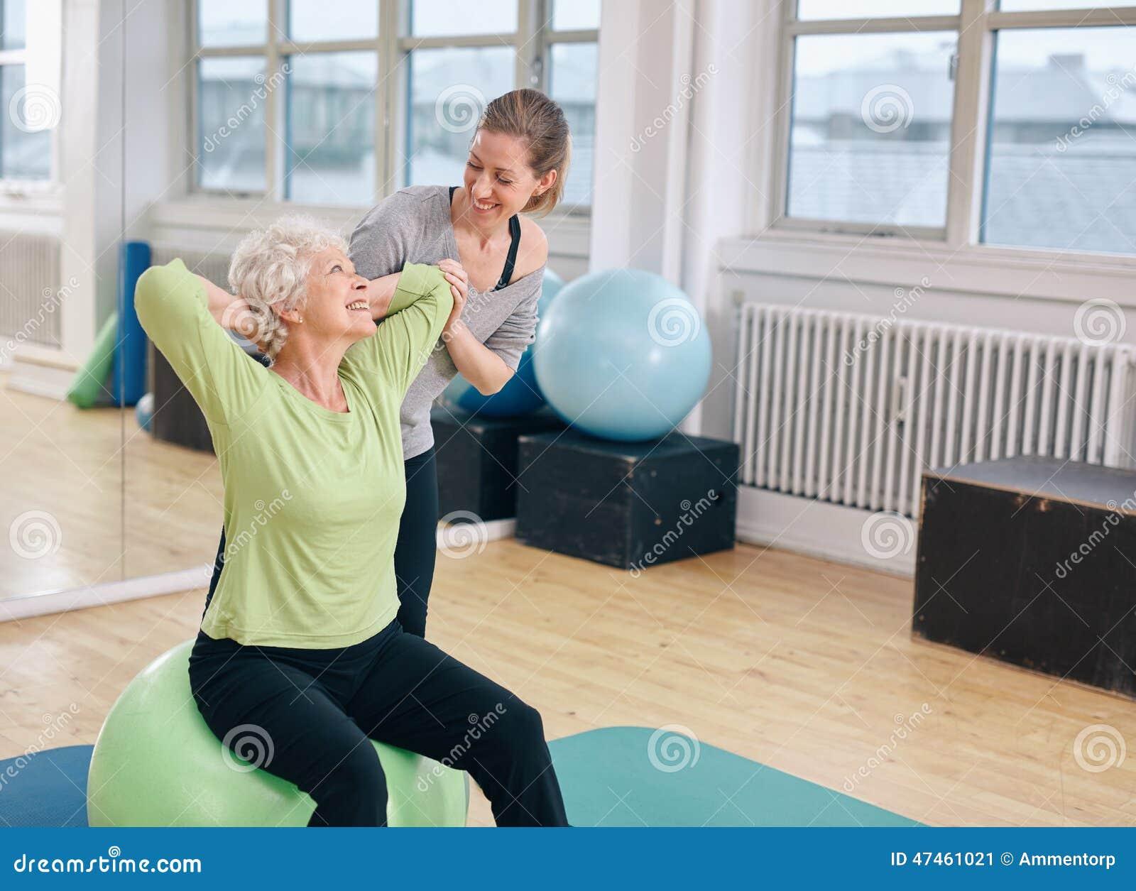 Lycklig hög kvinna som övar med den kvinnliga instruktören