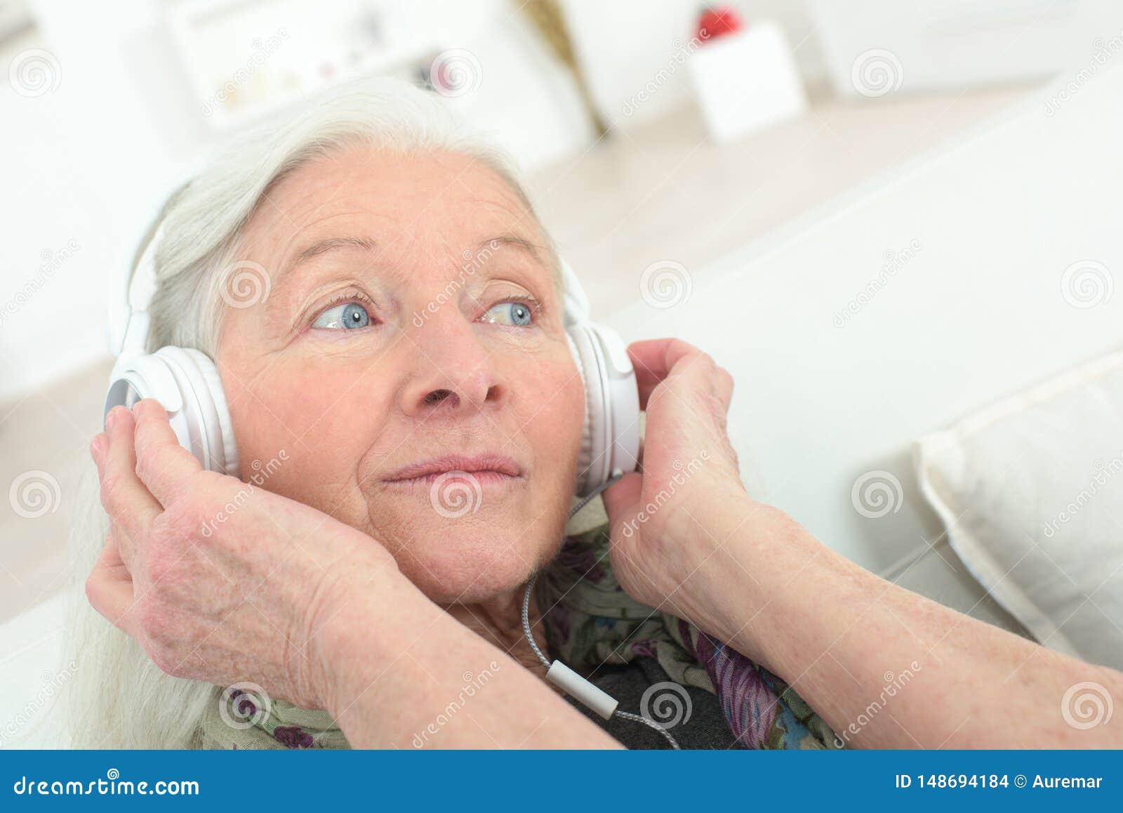 Lycklig h?g kvinna som hemma tycker om musik med headphonen