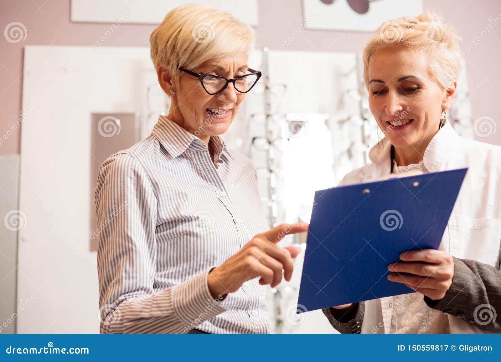 Lycklig hög kvinnlig patient som konsulterar med den mogna optometrikern