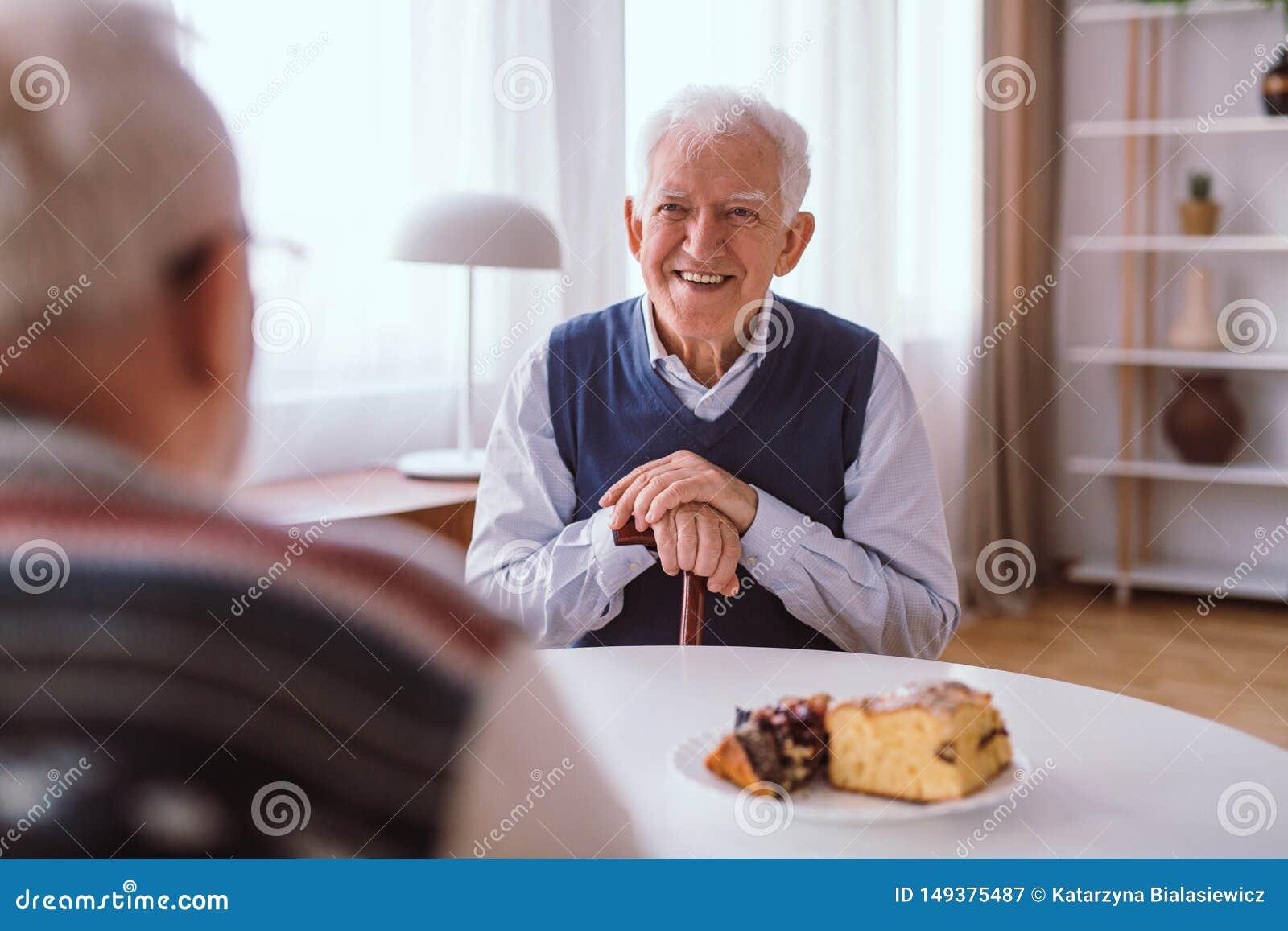 Lycklig h?g man som skrattar med hans gammal v?n ?ver stycket av kakan