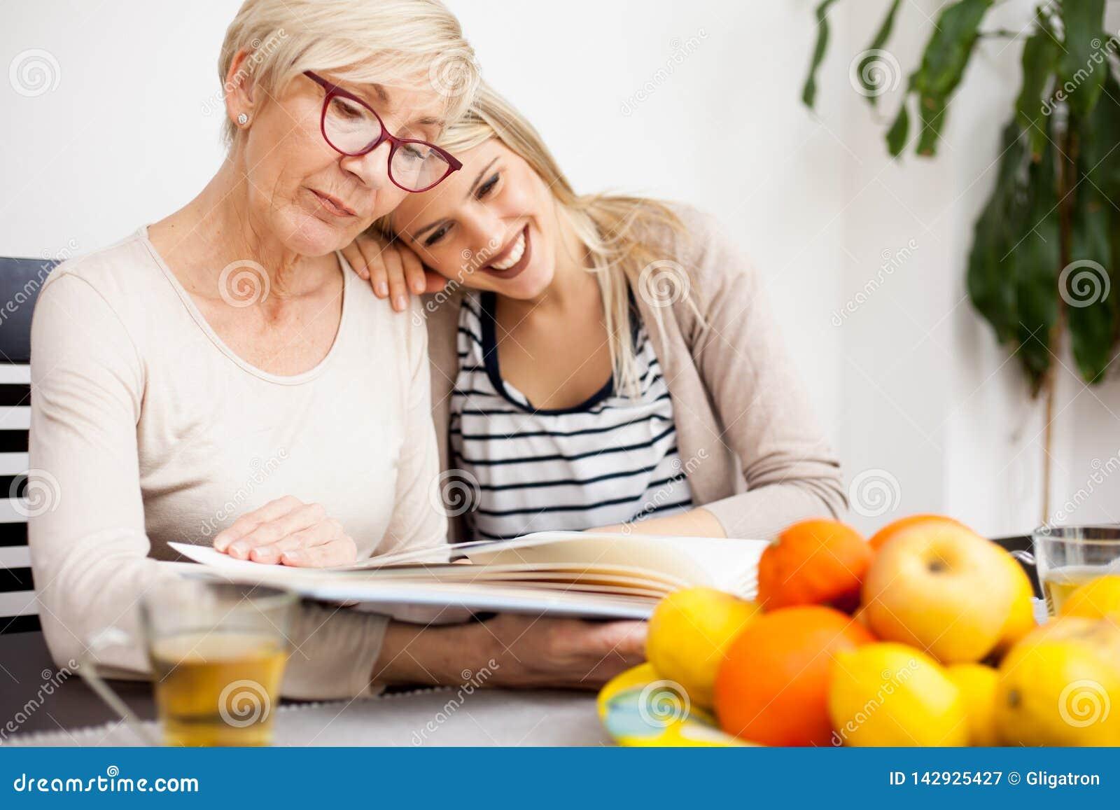Lycklig hög moder och hennes dotter som ser familjfotoalbumet, medan sitta på en äta middag tabell Dotters huvud som vilar på kvi