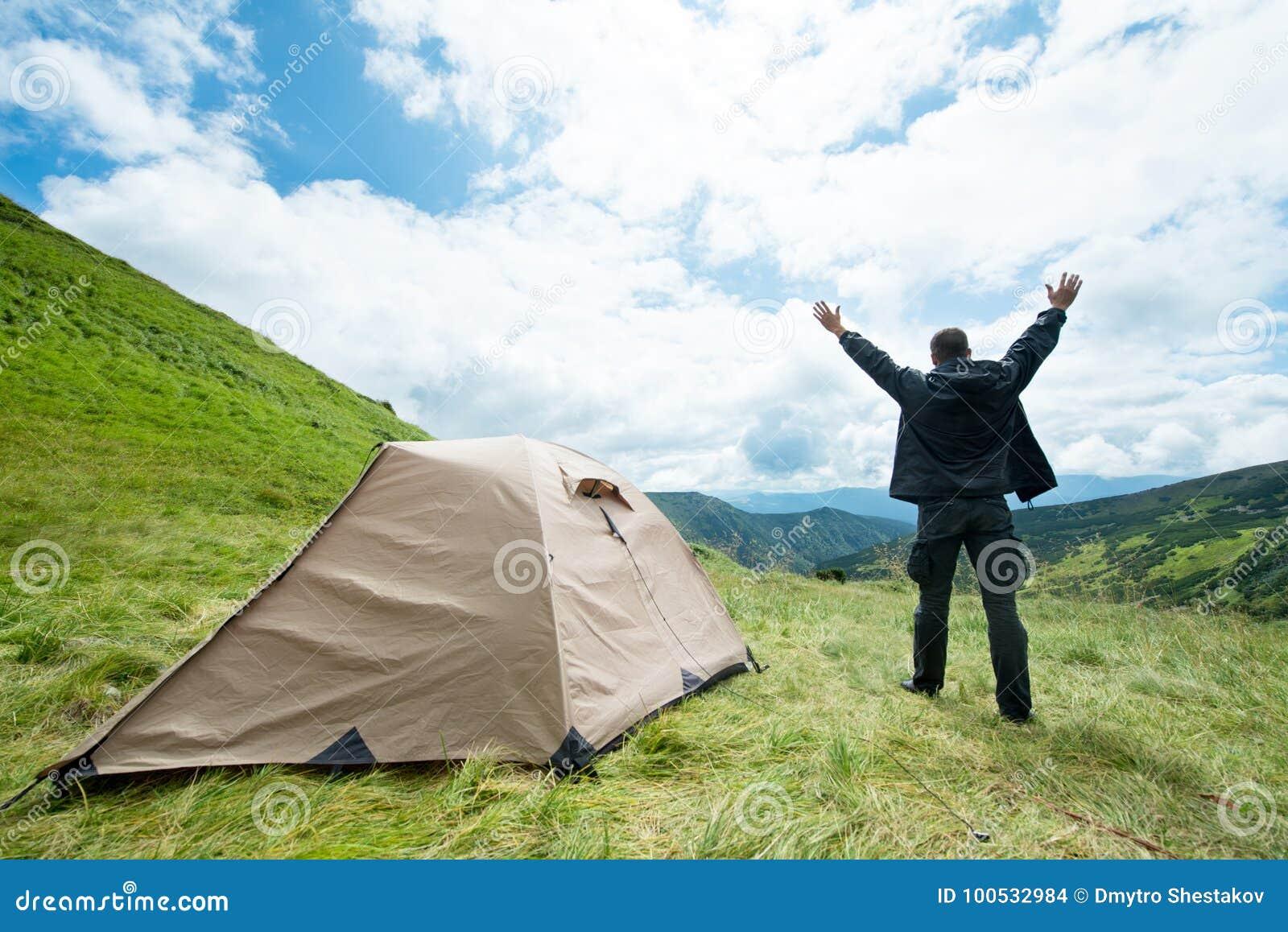 Lycklig handelsresande i bergen nära tältet