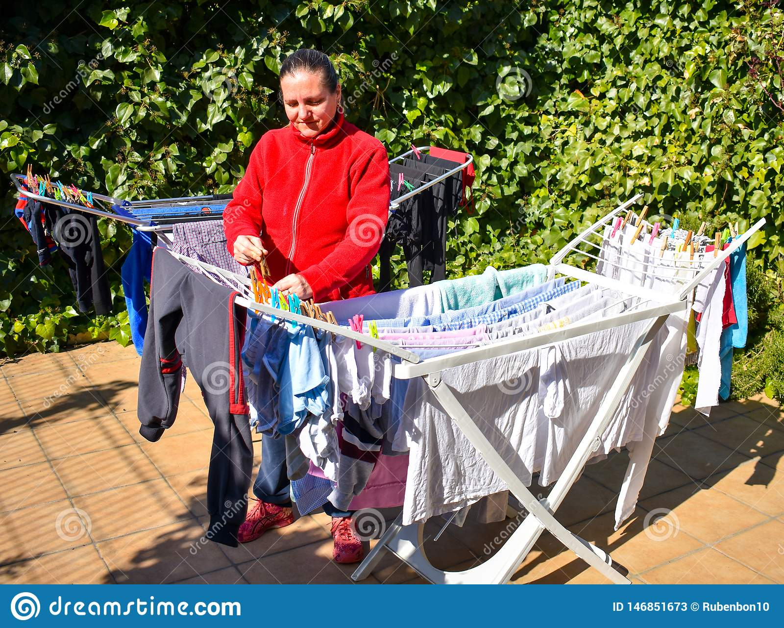 Lycklig hemmafru som rymmer den våta kläderna som tas precis bort från tvättmaskinen i den tvättande linjen pålagd terrassen av e