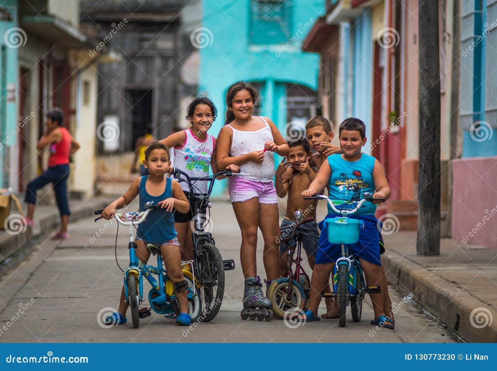 Lycklig kubansk barnstående i fattig färgrik kolonial gatagränd med leendeframsidan, i gammal stad, Kuba, Amerika