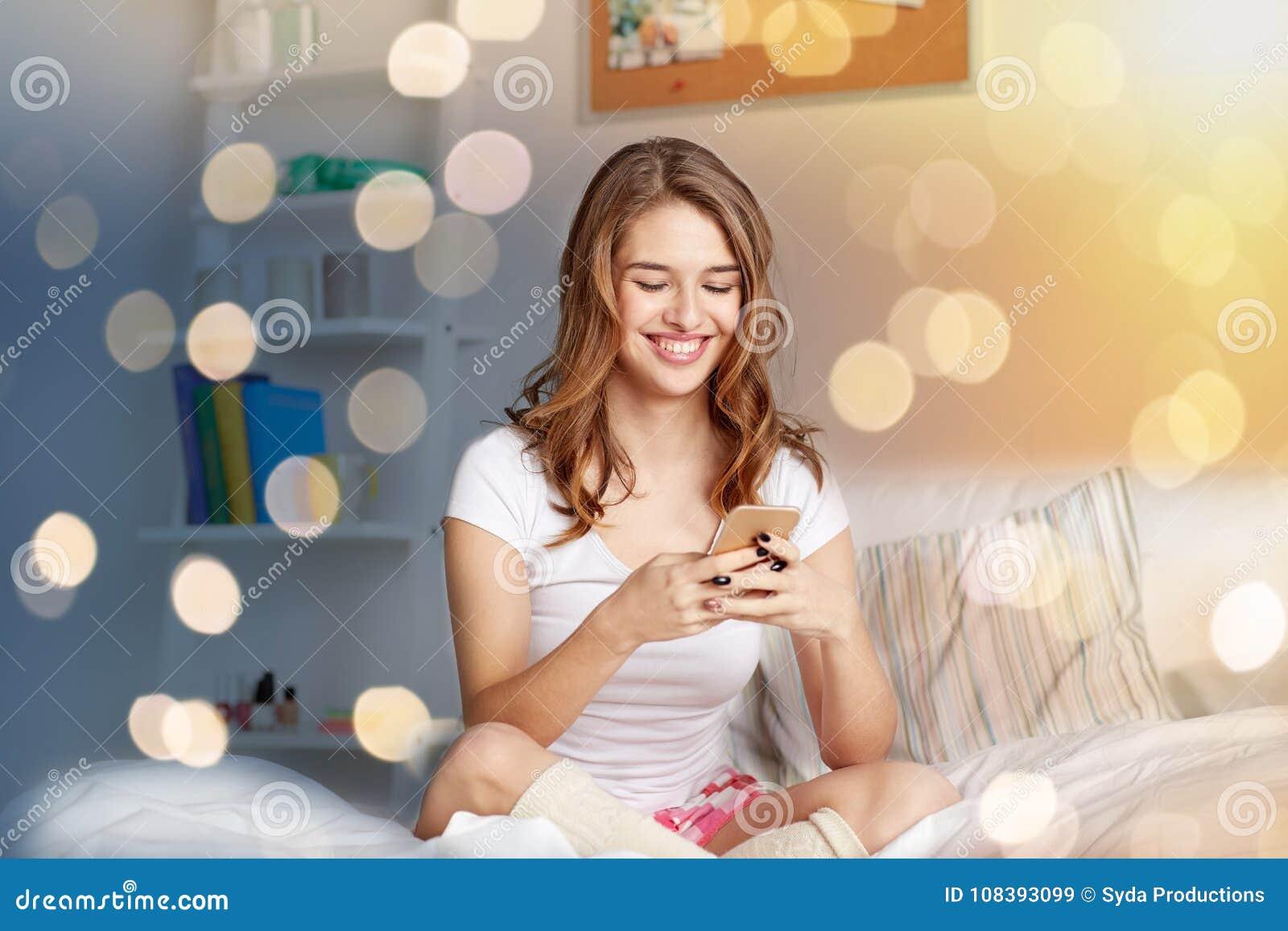 Lycklig kvinna eller flicka med smartphonen i säng hemma