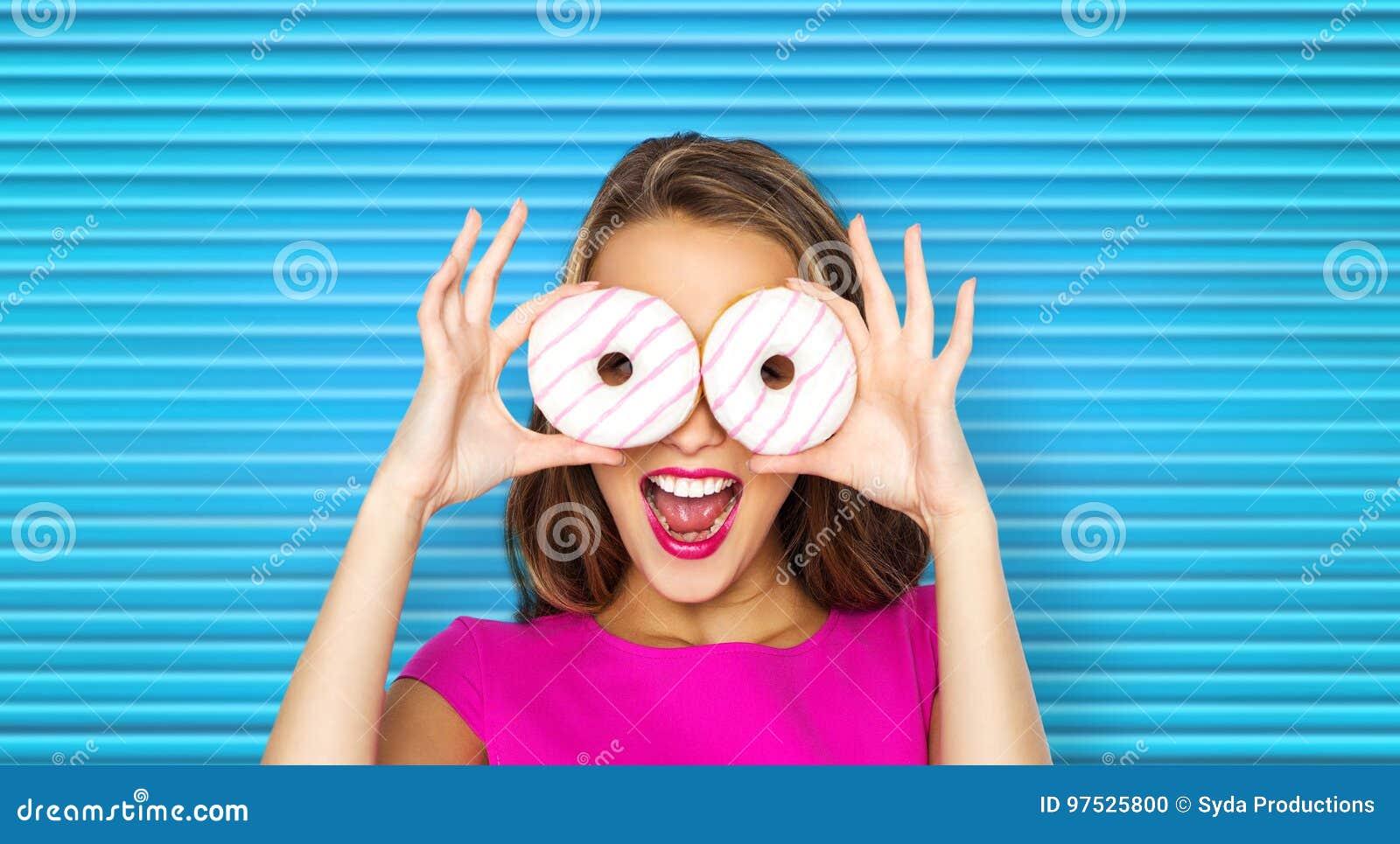 Lycklig kvinna eller tonårig flicka som ser till och med donuts