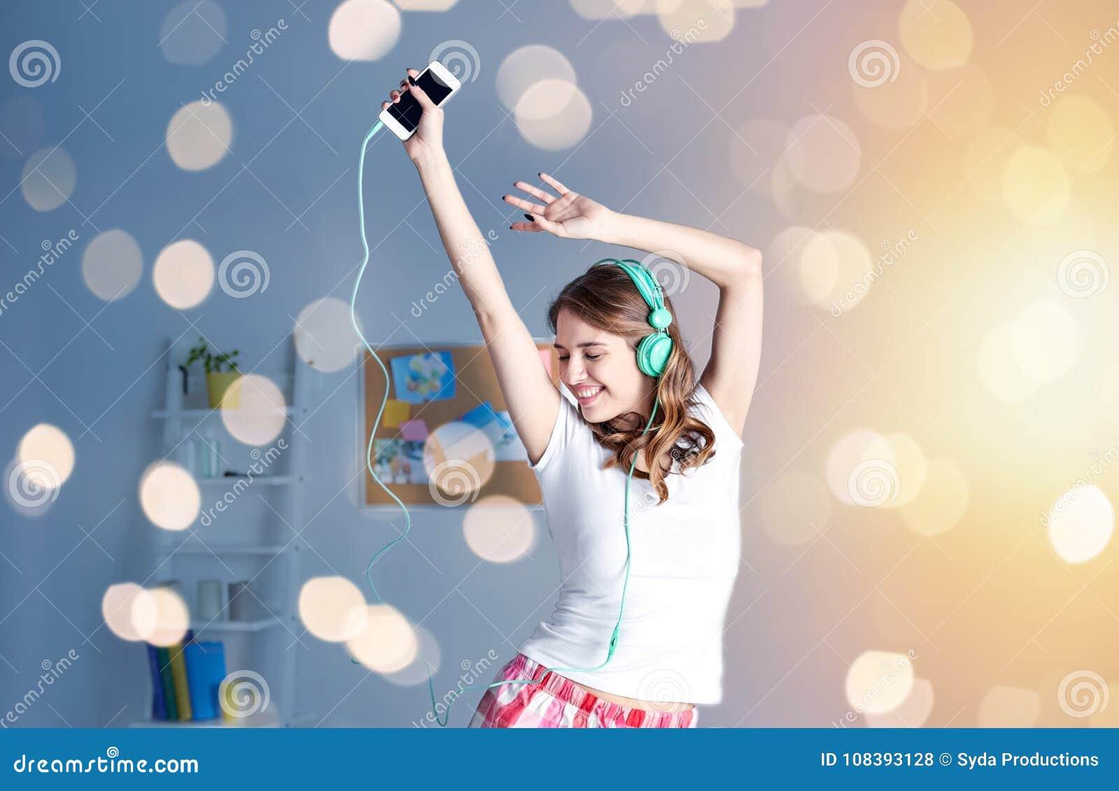 Lycklig kvinna i hörlurar som ihaving roligt hemmastatt