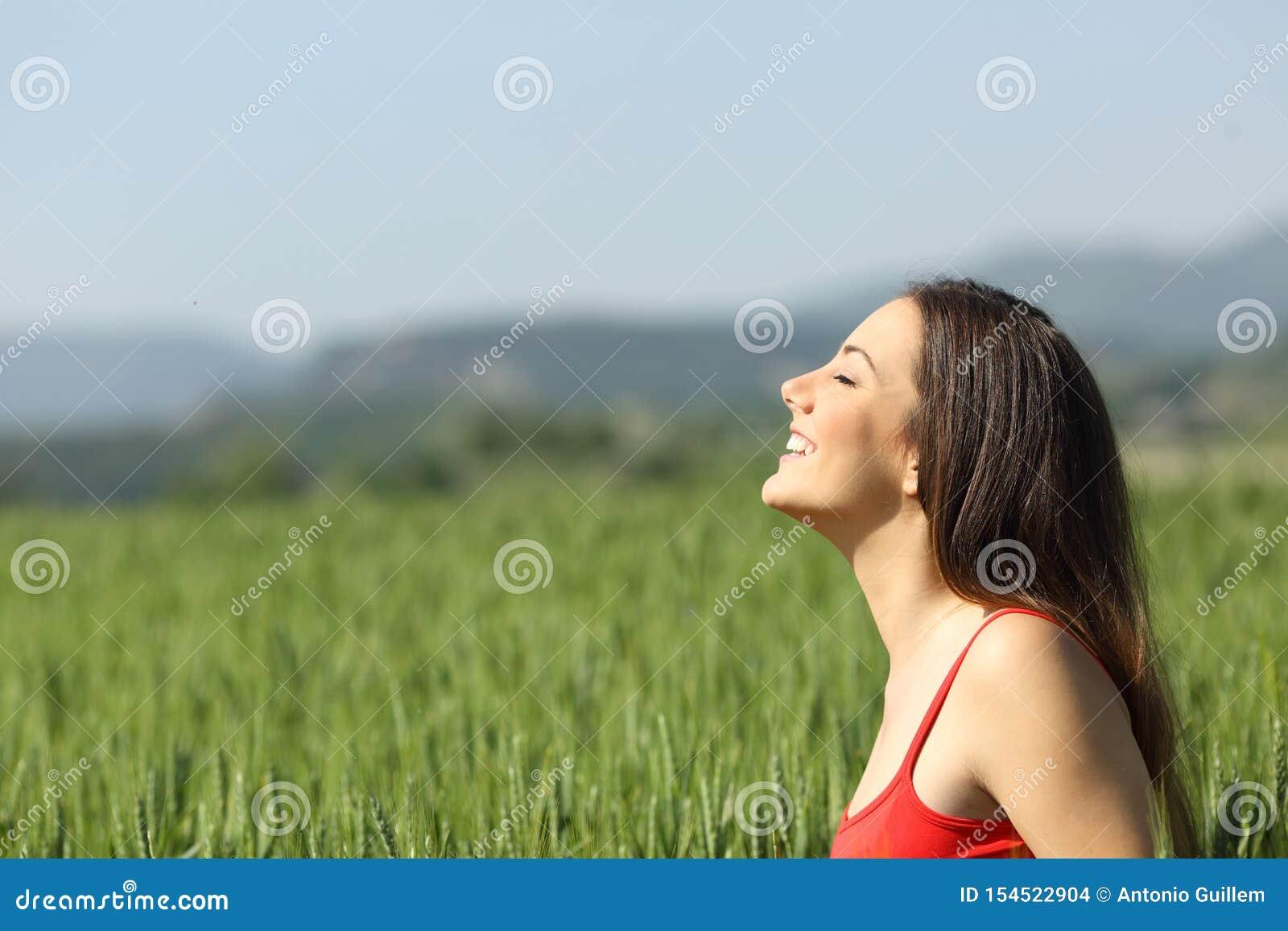 Lycklig kvinna i rött ny luft för andas i ett fält