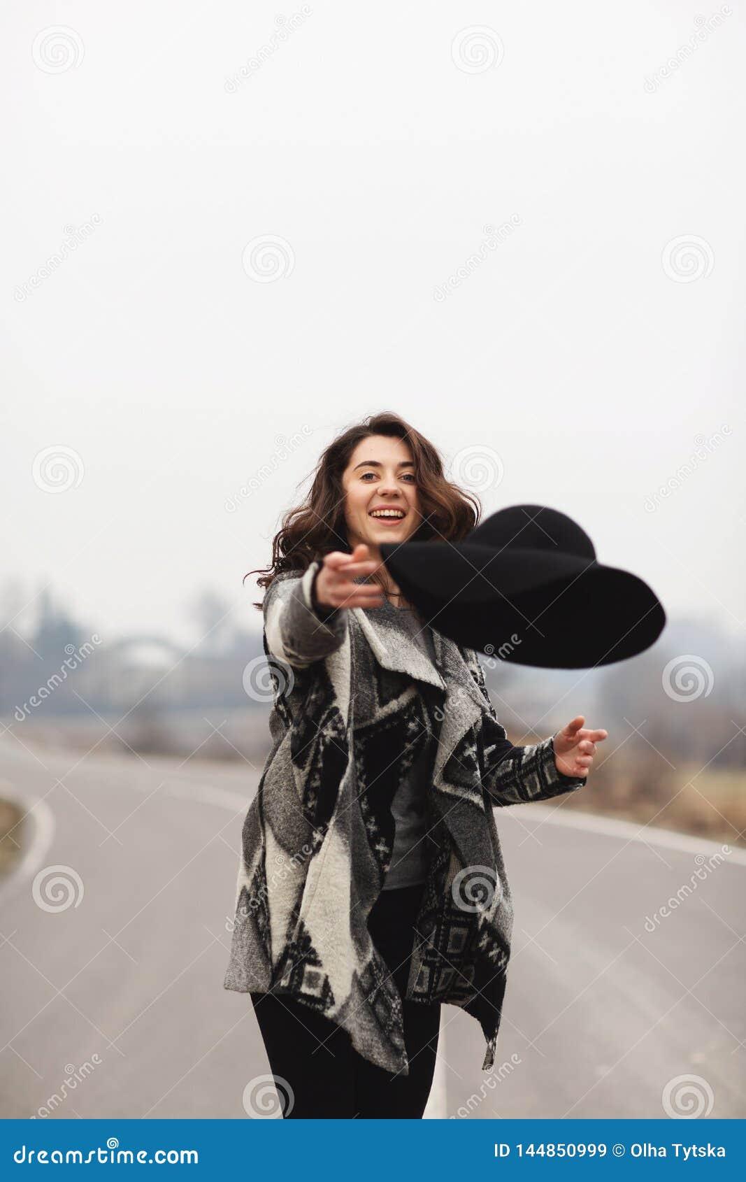 Lycklig kvinna i ritter för en härlig grå kofta och för svart hatt längs vägen