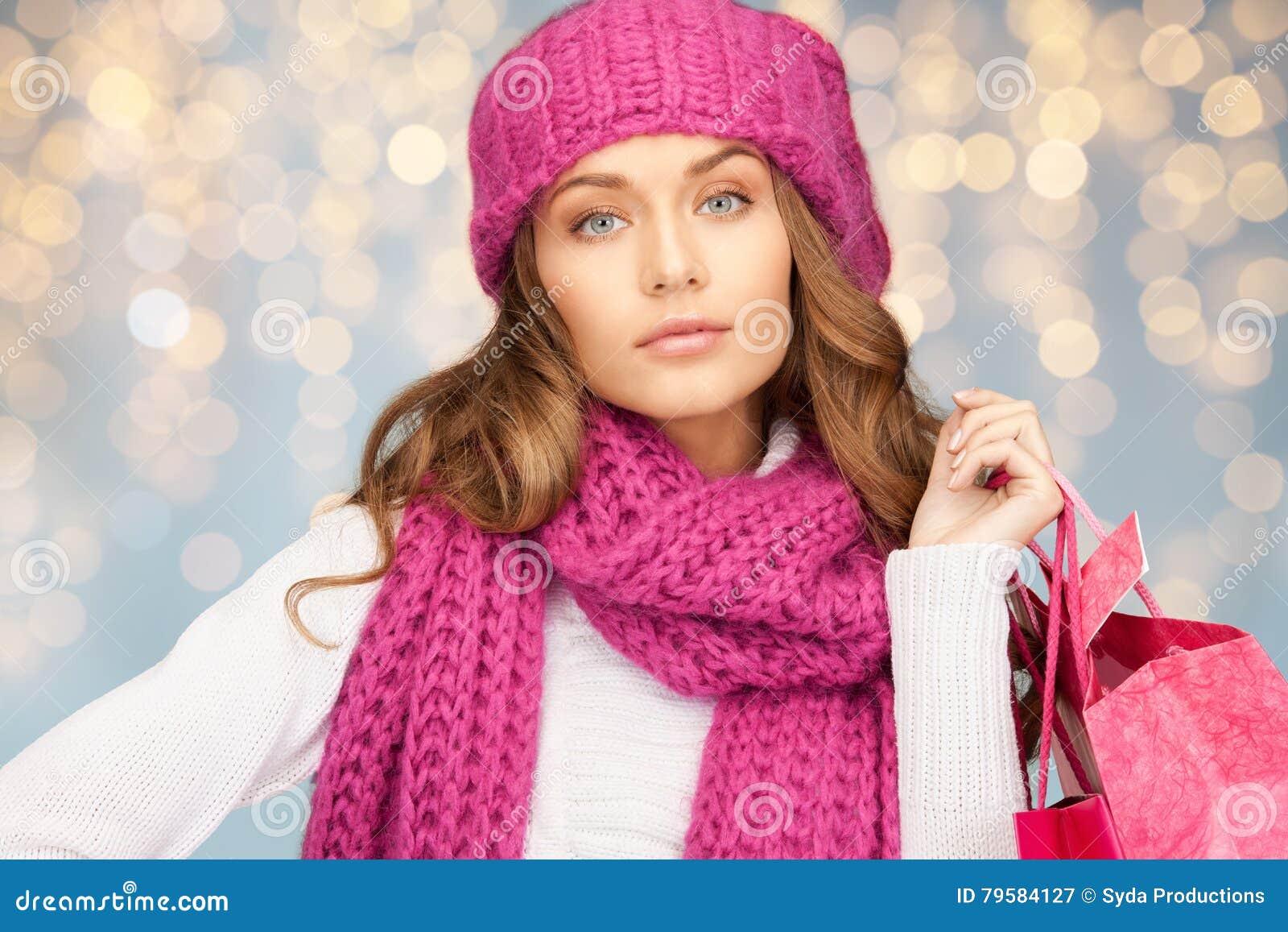 Lycklig kvinna i vinterkläder med shoppingpåsar