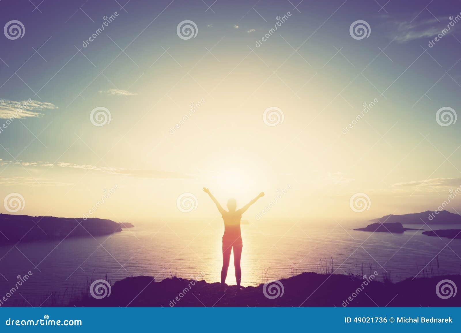 Lycklig kvinna med händer upp på klippan över havet och öar på solnedgången
