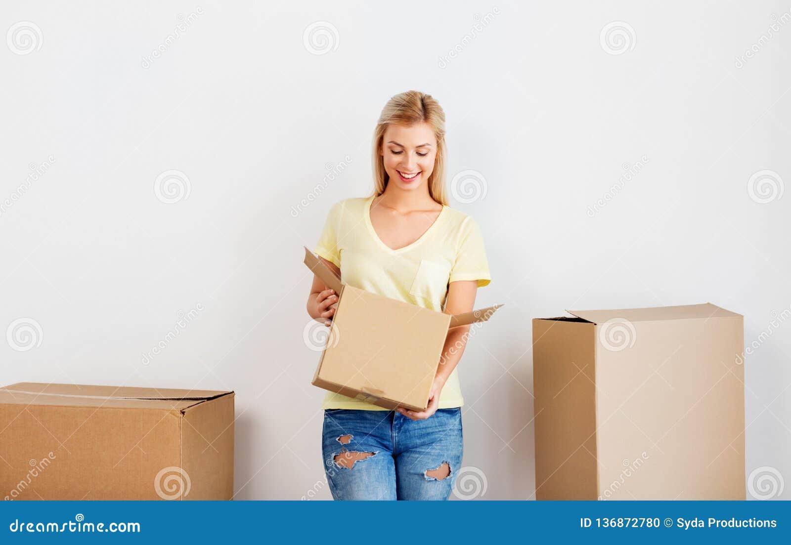 Lycklig kvinna med kartongen som flyttar sig till det nya hemmet