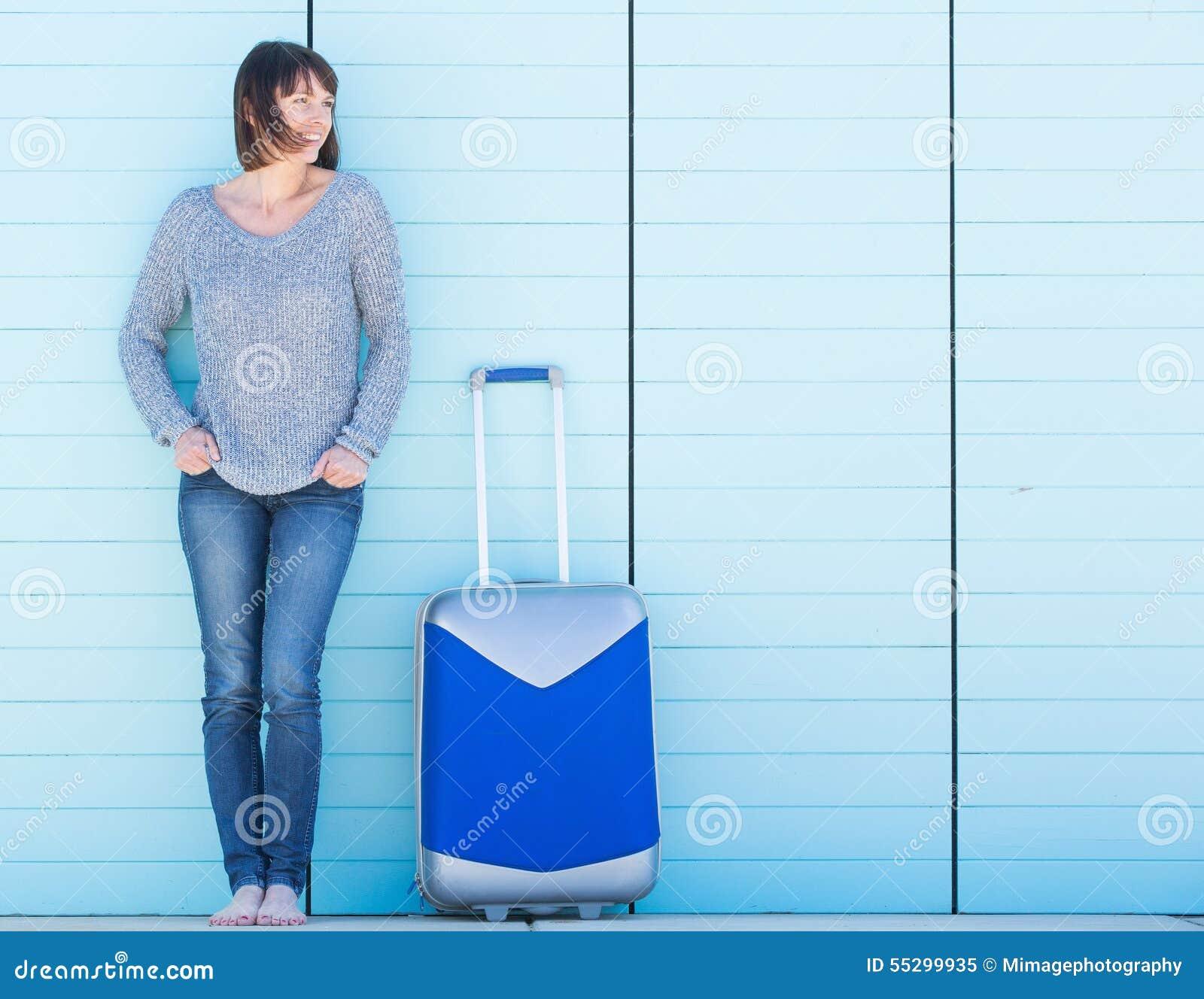 Lycklig kvinna på semester som ler med resväskan