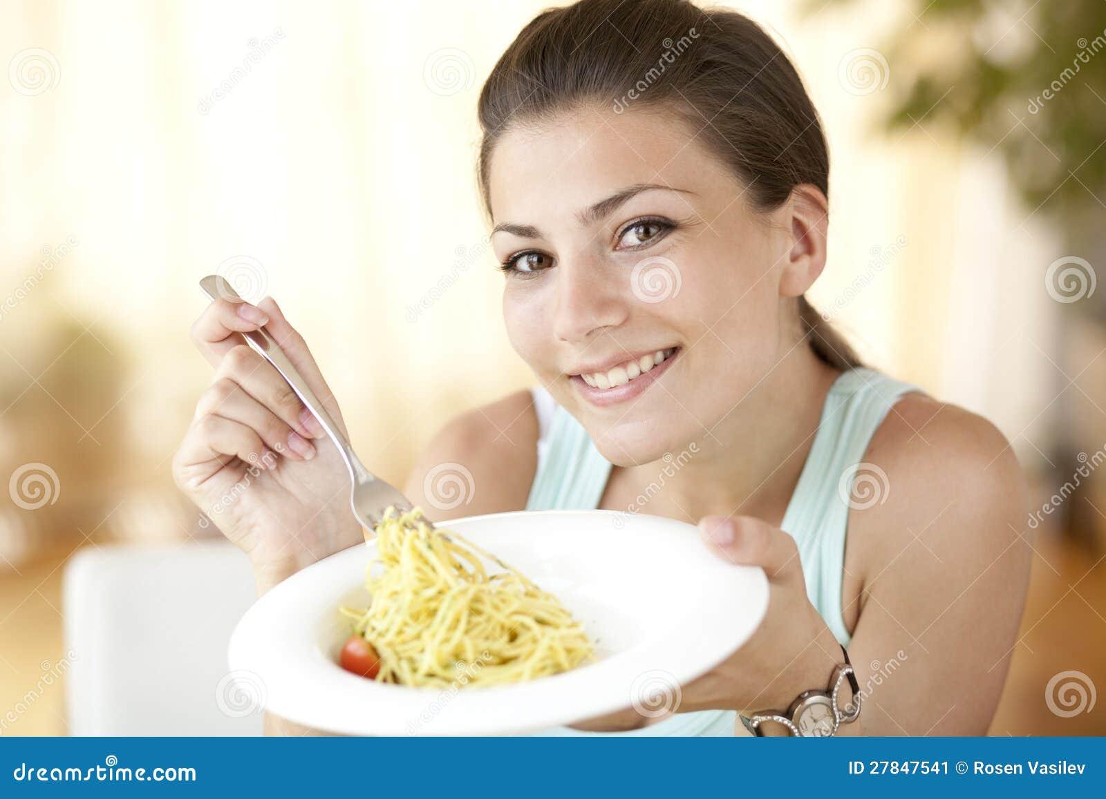 Lycklig kvinna som äter spagetti