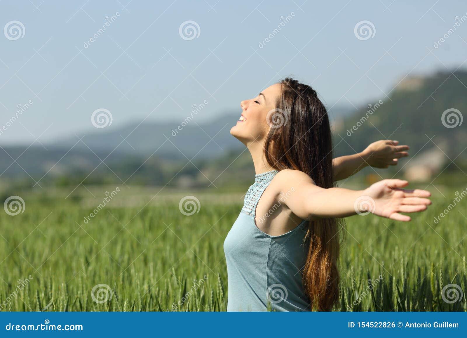 Lycklig kvinna som andas djupt ny luft i ett fält