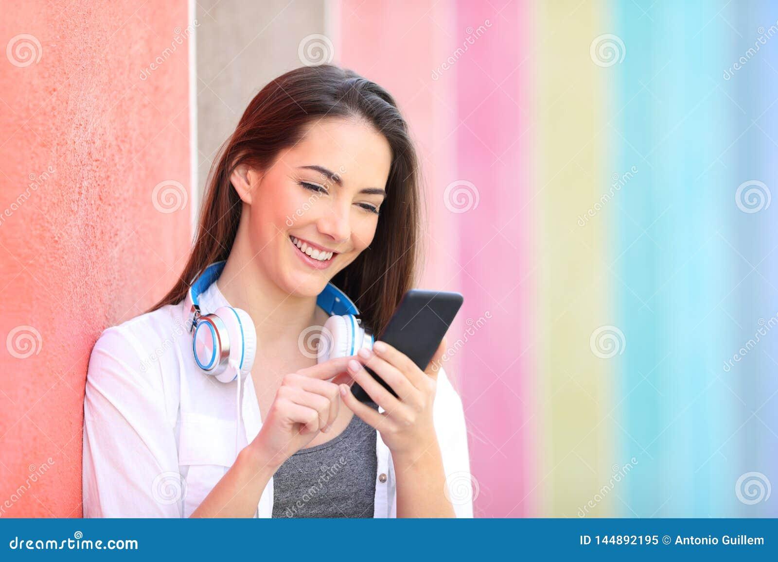 Lycklig kvinna som anv?nder den smarta telefonen som lutar i en v?gg