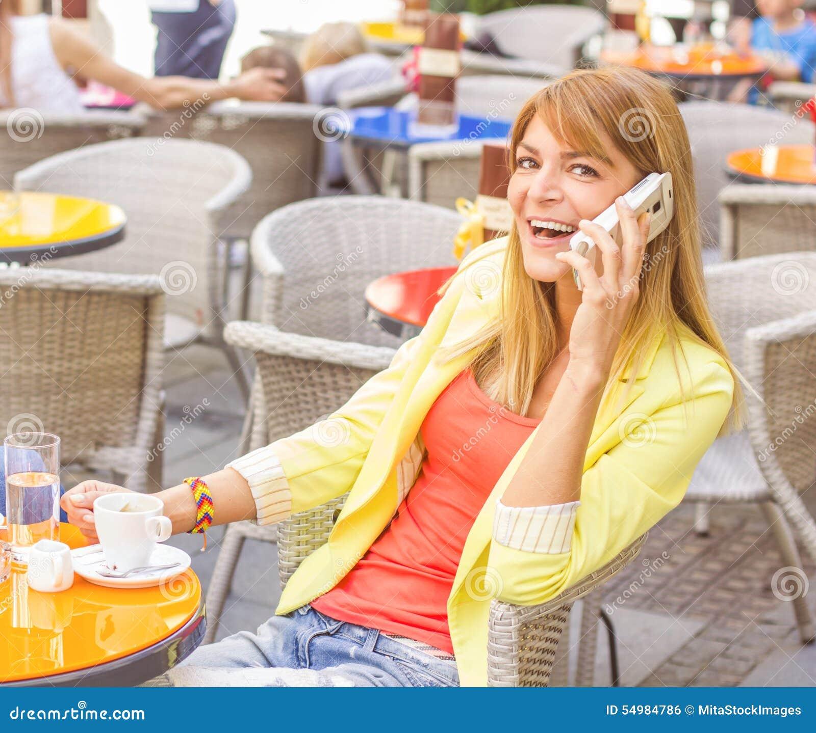 Lycklig kvinna som använder mobiltelefonen