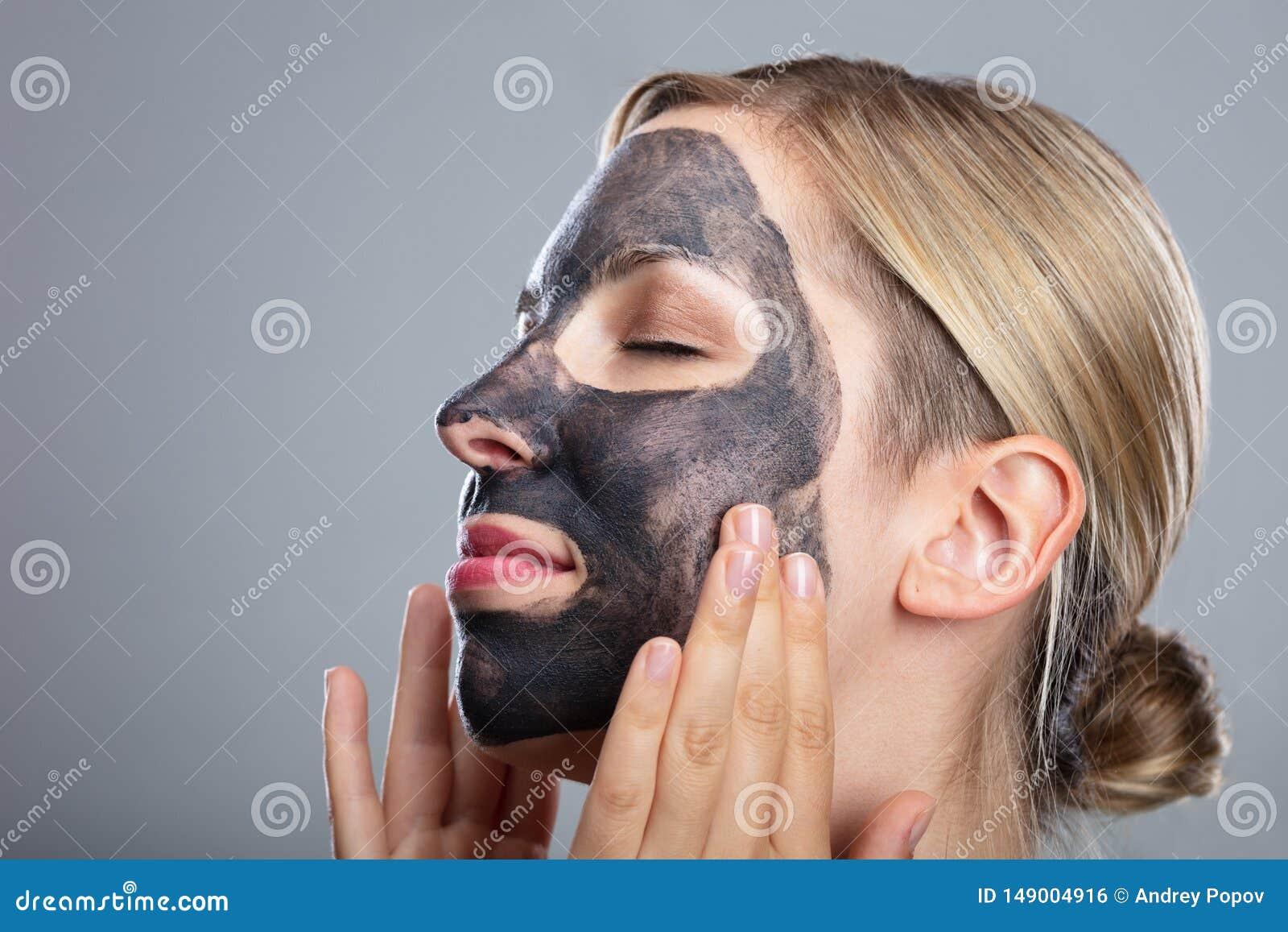 Lycklig kvinna som anv?nder framsidamaskeringen f?r aktiverat kol