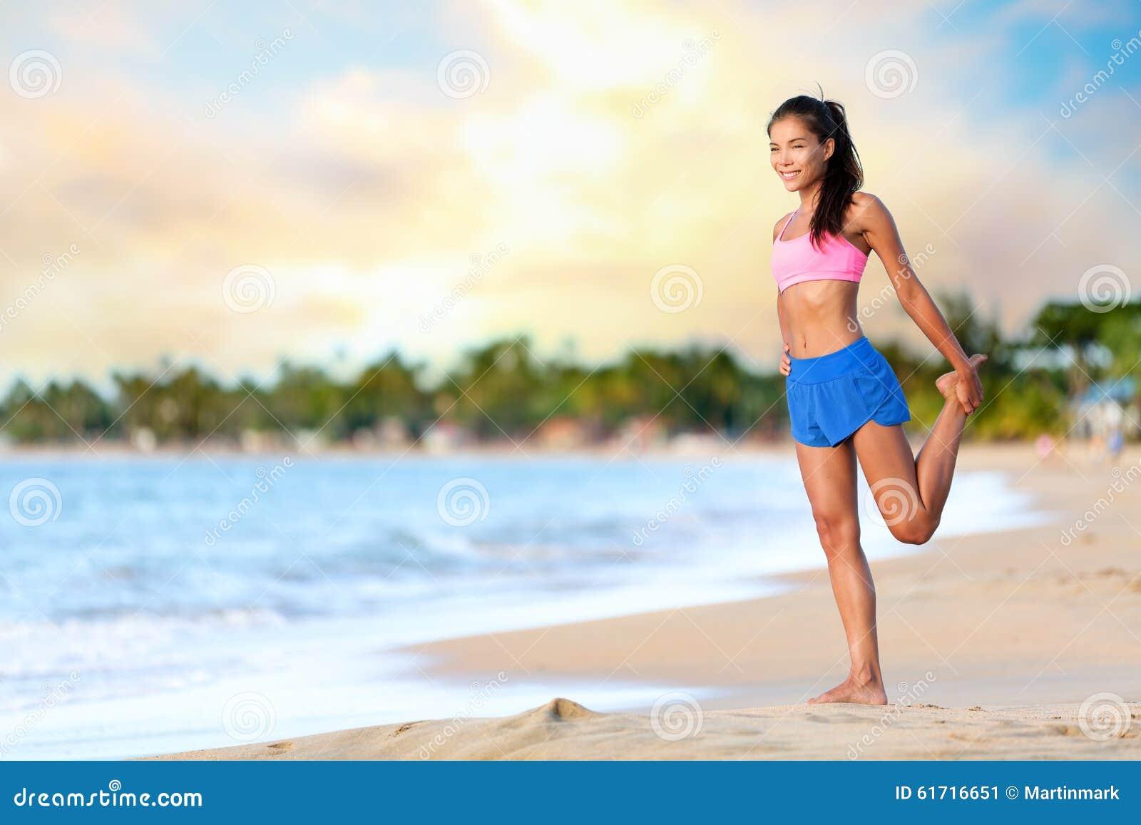 Lycklig kvinna som gör sträcka övning på stranden