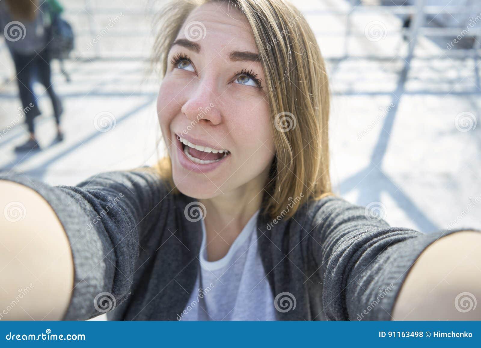 Lycklig kvinna som gör utomhus- selfie
