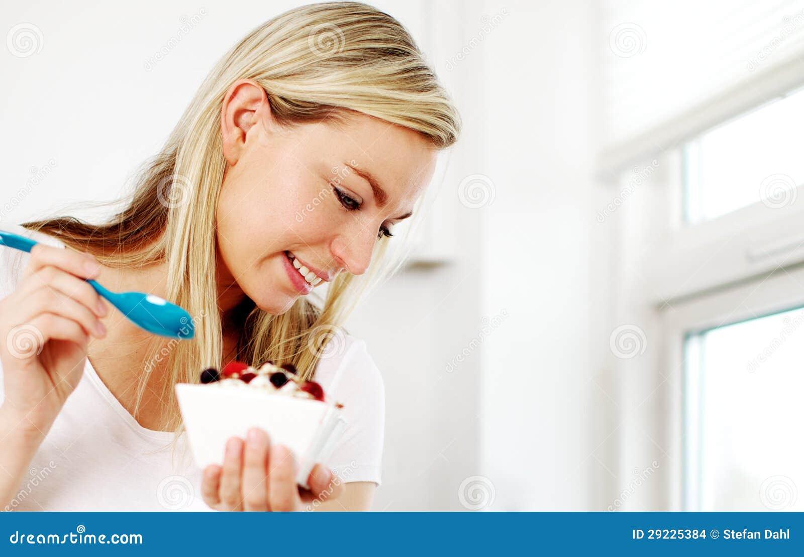 Lycklig kvinna som har en sund frukost