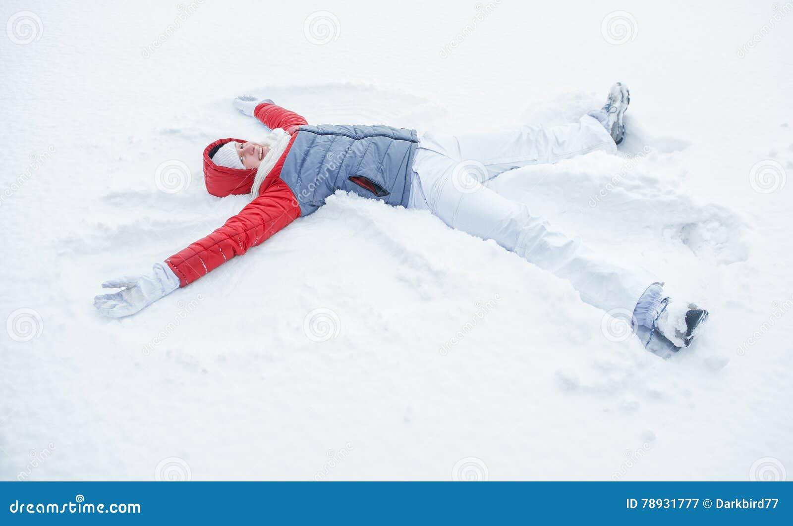 Lycklig kvinna som har gyckel på insnöad vinter