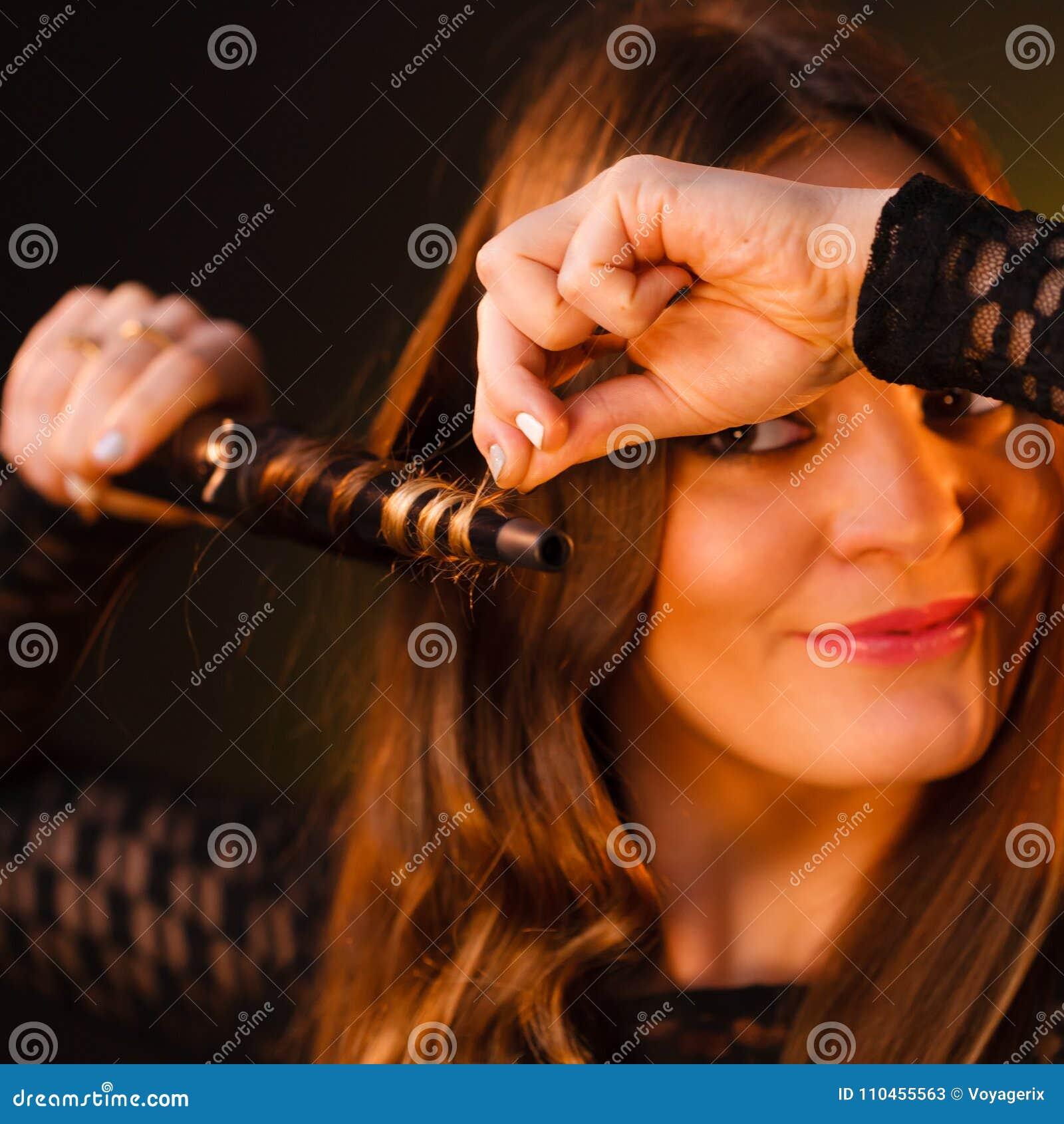Lycklig kvinna som krullar hennes långa bruna hår