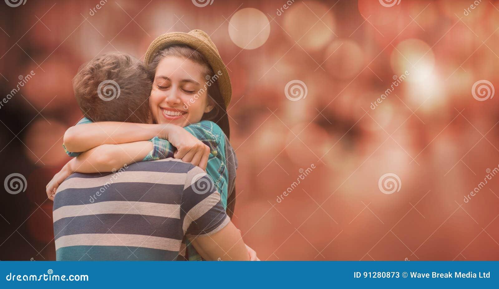 Lycklig kvinna som omfamnar mannen över suddighetsbakgrund