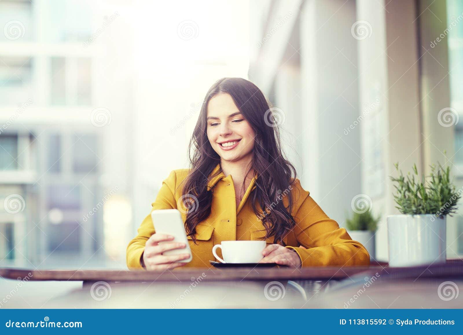 Lycklig kvinna som smsar på smartphonen på stadskafét