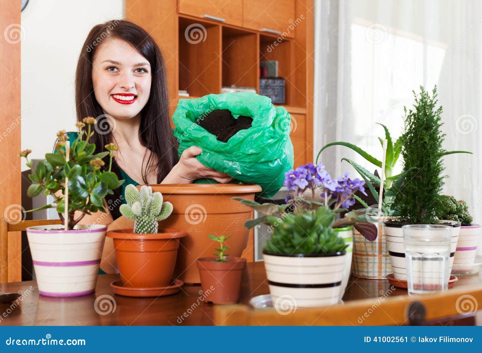 Lycklig kvinna som transplanterar lade in blommor