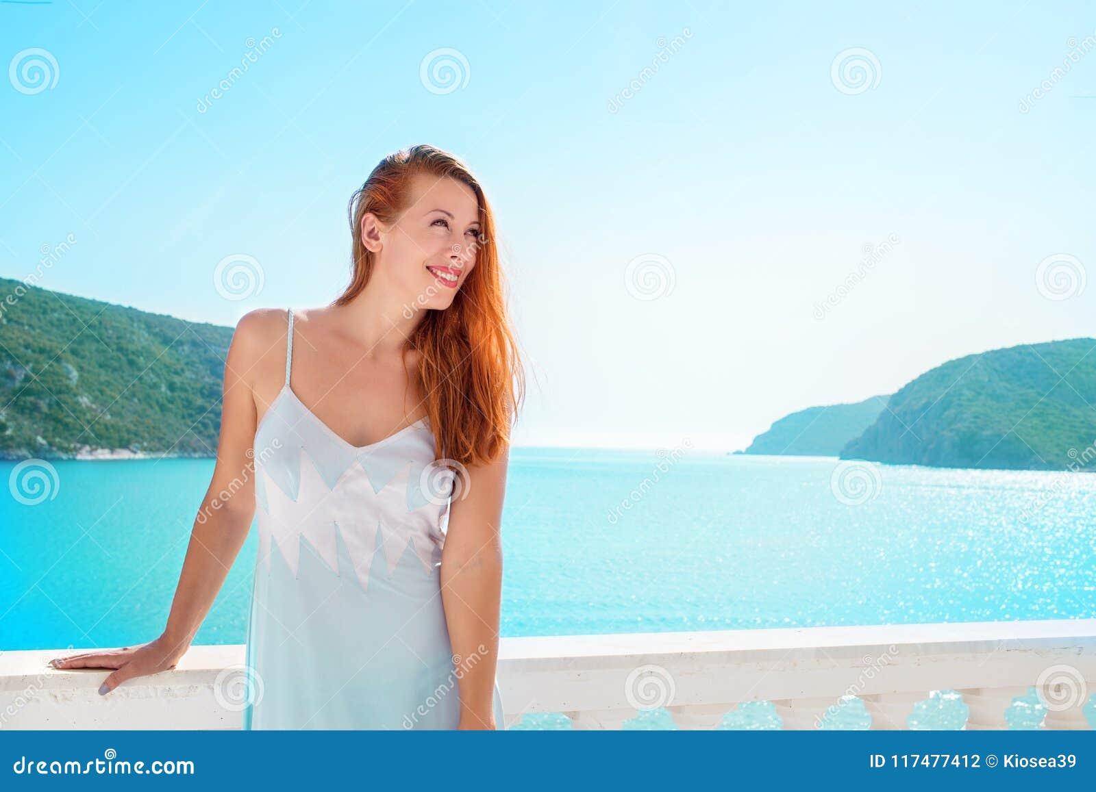 Lycklig kvinna som tycker om den lyxiga semesterorten på havet