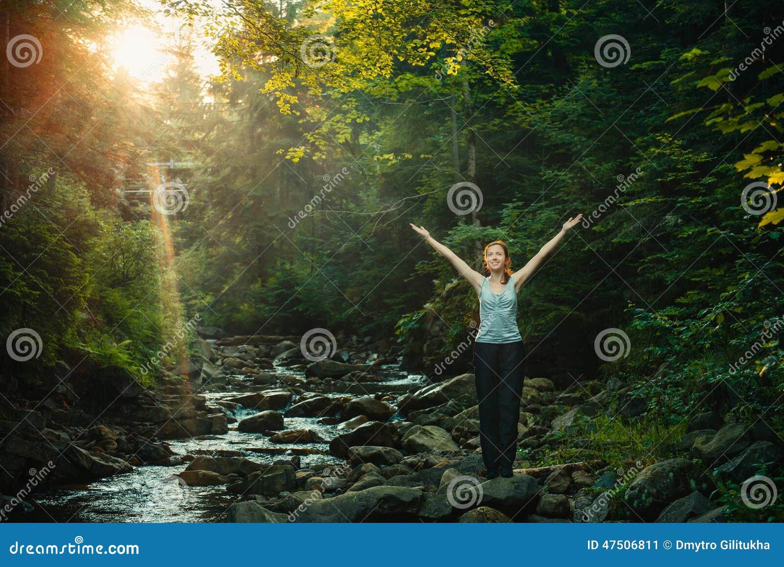 Lycklig kvinna som tycker om naturen i skog