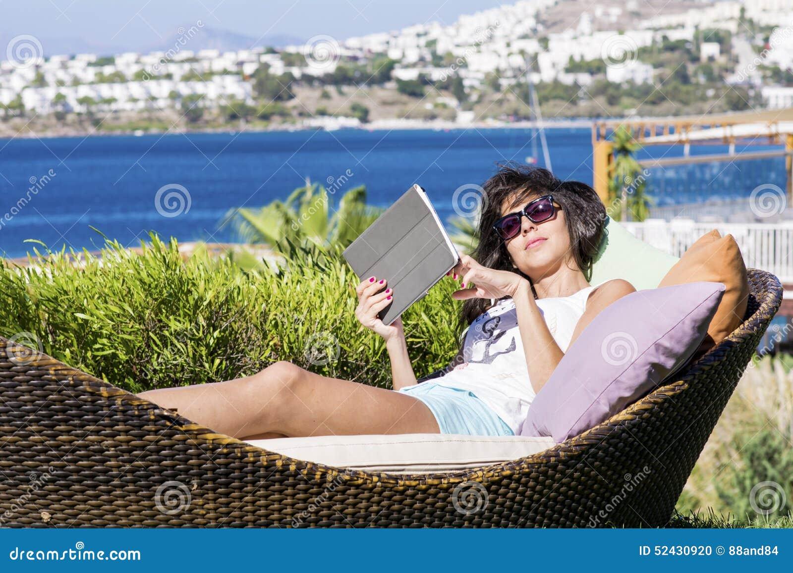 Lycklig kvinna som tycker om sommarsemestern med minnestavlan i händerna