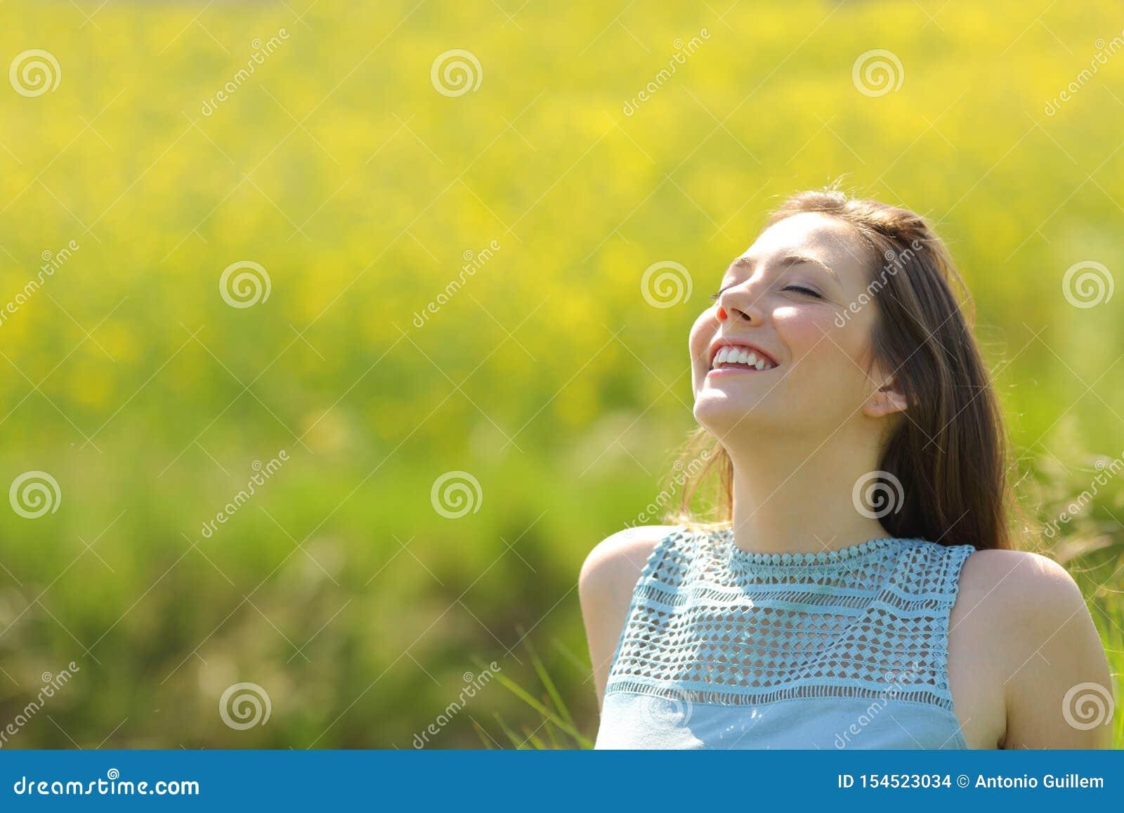 Lycklig kvinna som vilar andas ny luft i ett fält