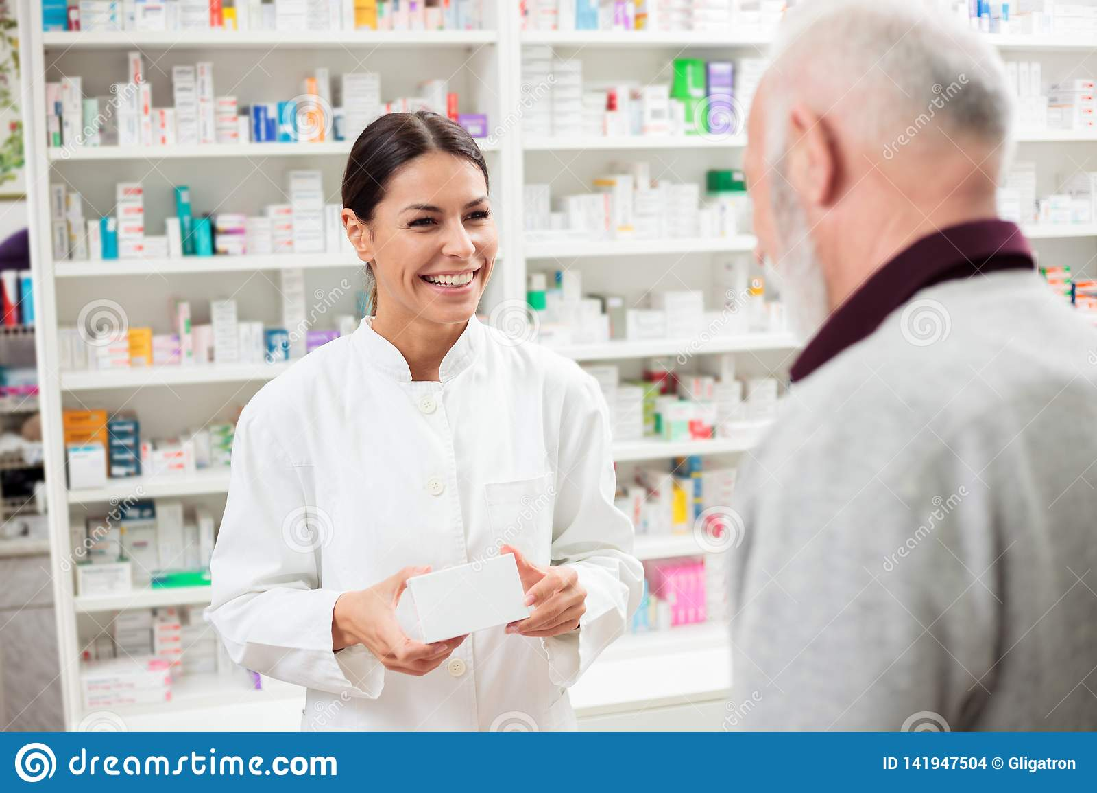 Lycklig kvinnlig apotekare som ger läkarbehandlingar till den höga manliga kunden