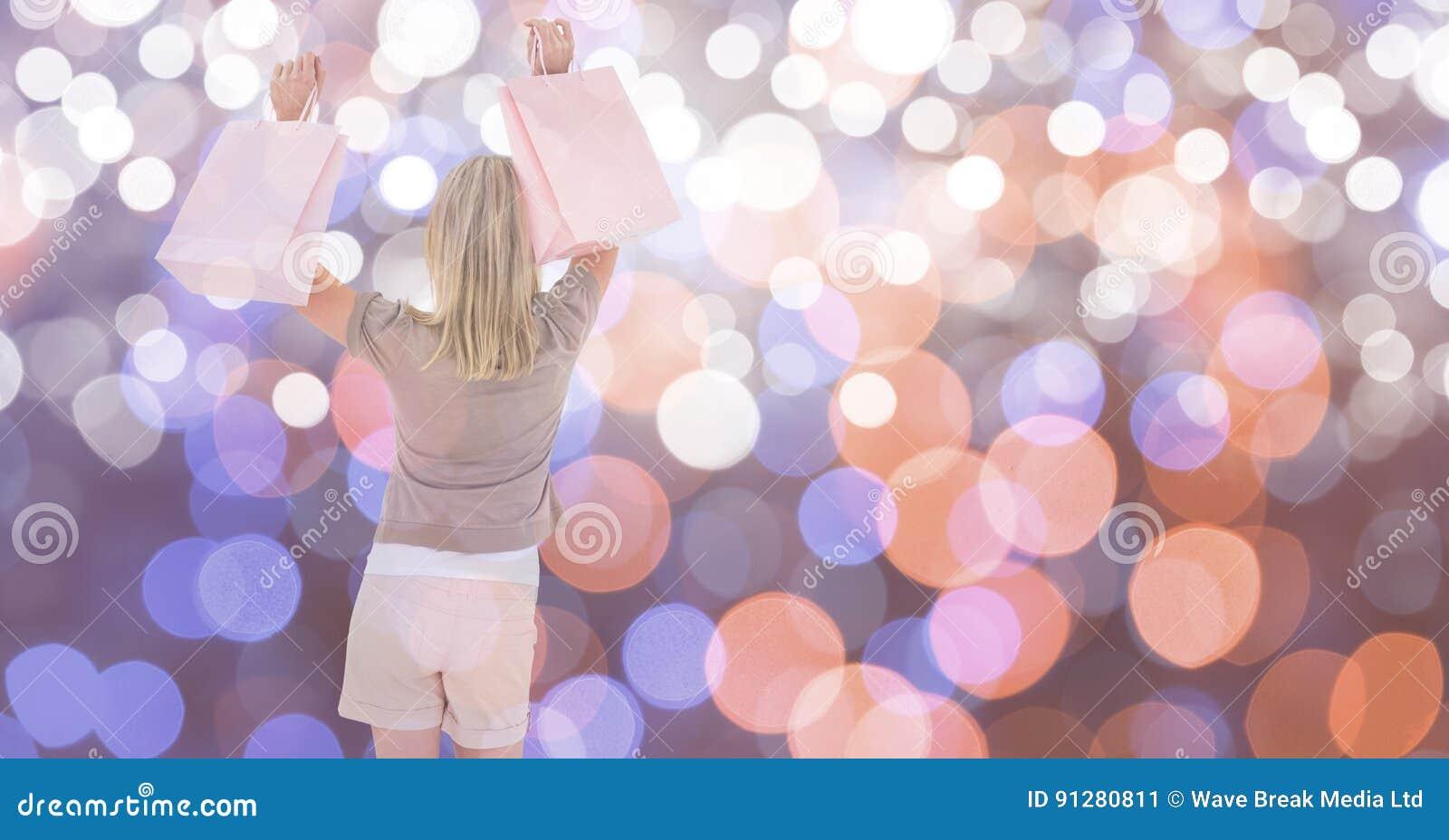Lycklig kvinnlig med shoppingpåsar över bokeh
