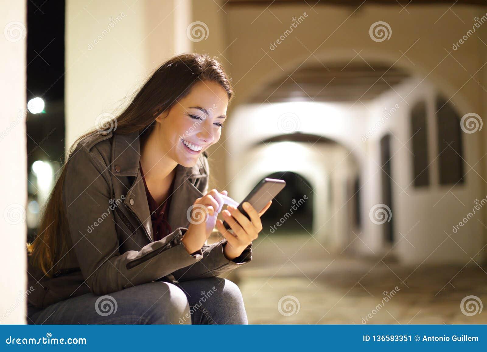 Lycklig kvinnlig som använder en smart telefon i natten i gatan