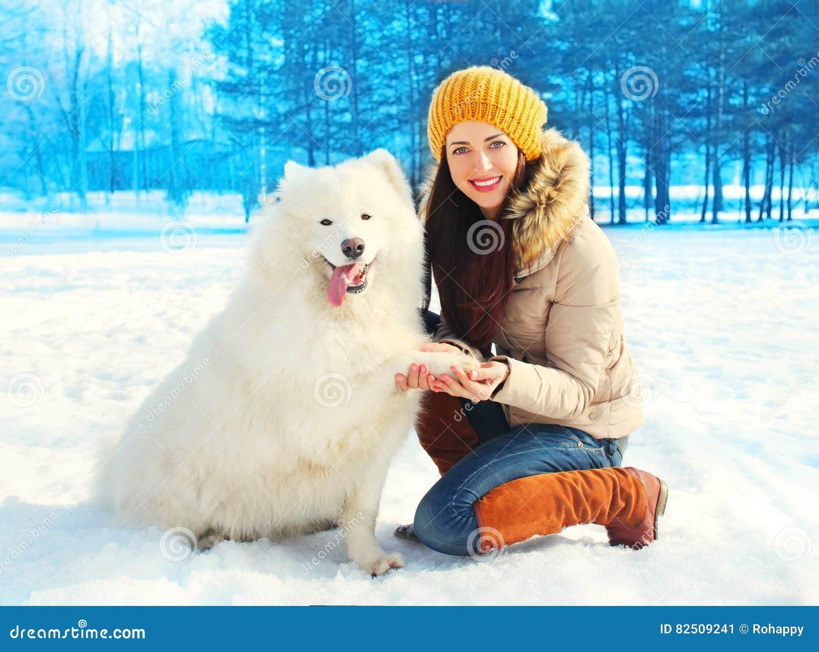 Lycklig le ägare för ung kvinna med den vita dagen för Samoyedhundvinter på snö