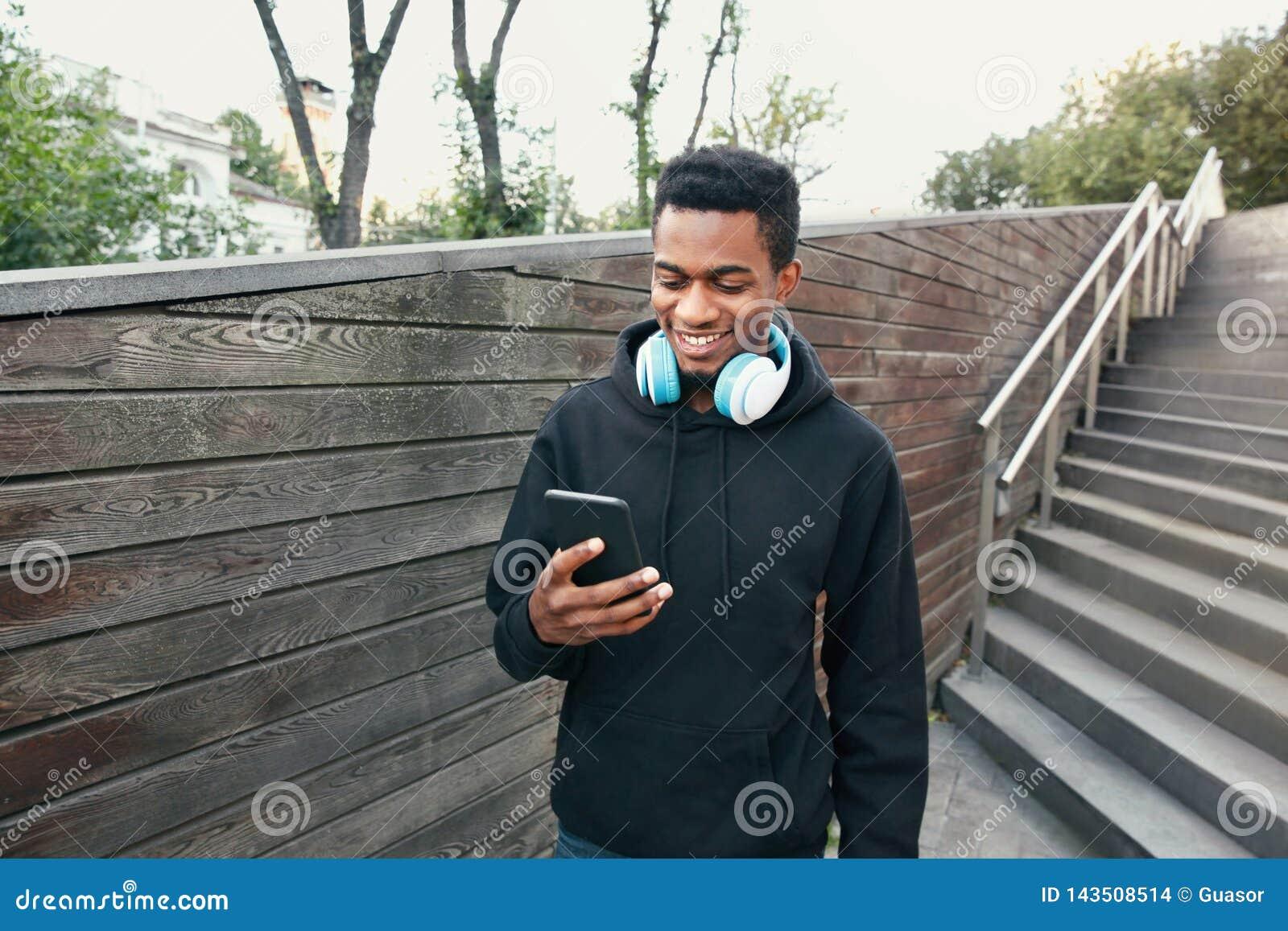 Lycklig le afrikansk man för stående med telefonen, hörlurar som lyssnar till musik som bär den svarta hoodien som går på stad