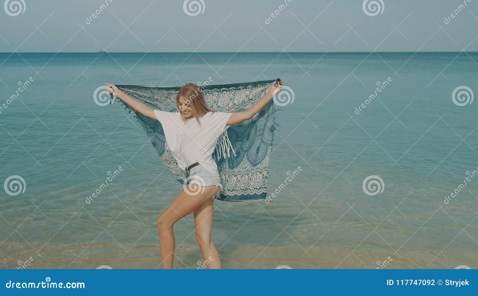 Lycklig le kvinna på stranden
