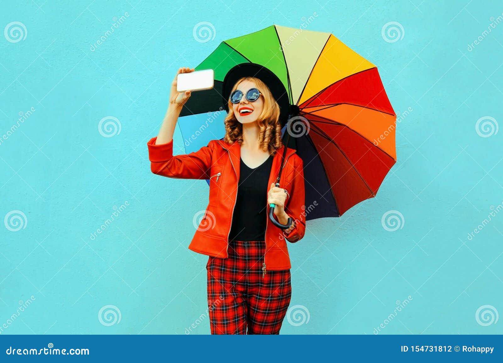 Lycklig le kvinna som tar selfiebilden vid telefonen med det färgrika paraplyet i det röda omslaget, svart hatt på den blåa vägge