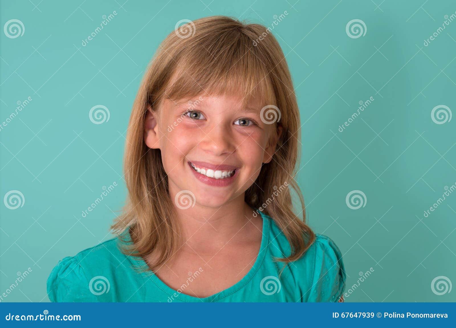 Lycklig le liten flicka a på turkosbakgrund sinnesrörelser