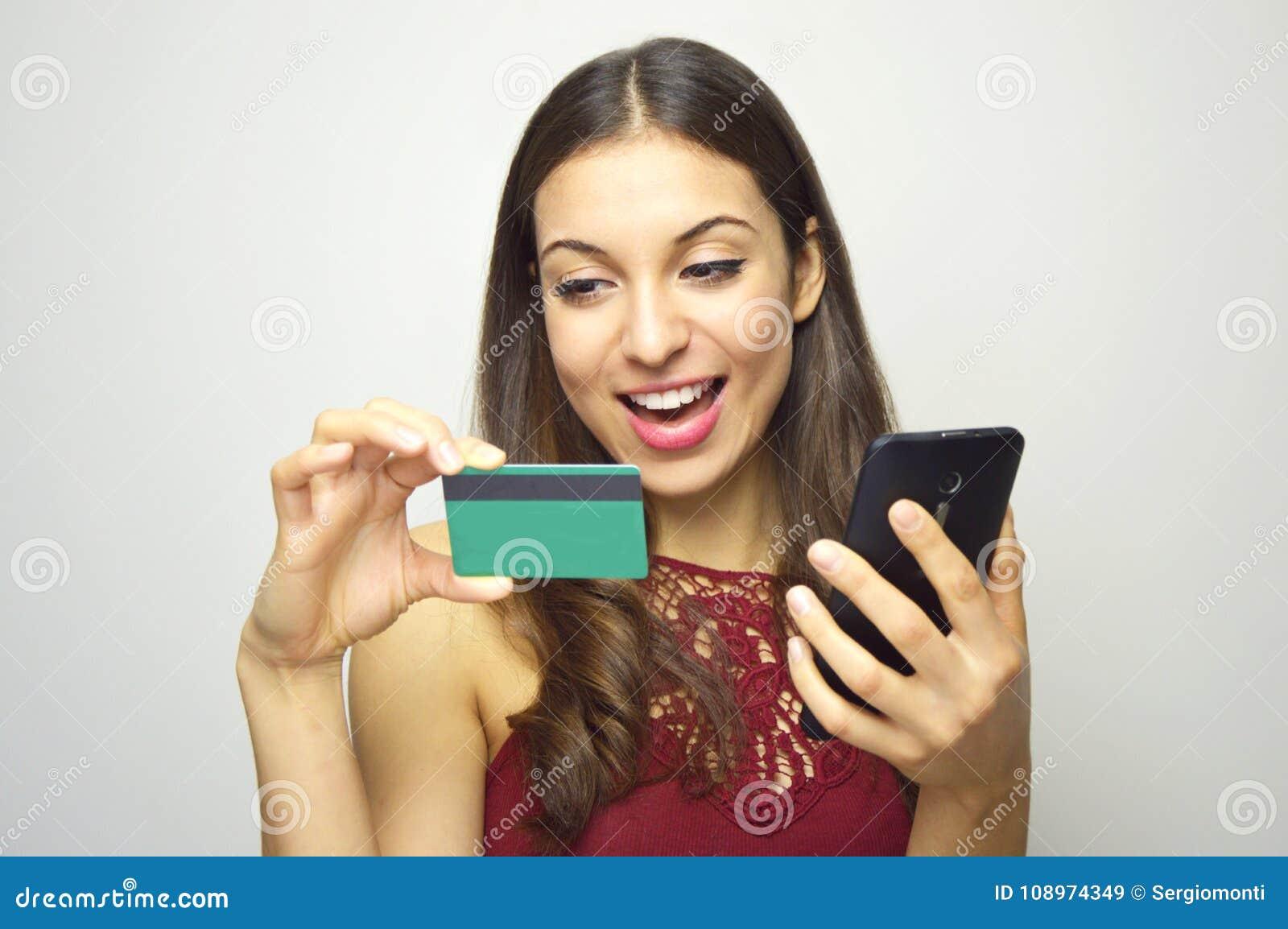 Lycklig le telefon och kreditkort för flickainnehav smart i hennes händer på vit bakgrund E-kommers kvinna Folk som gör shoppingn